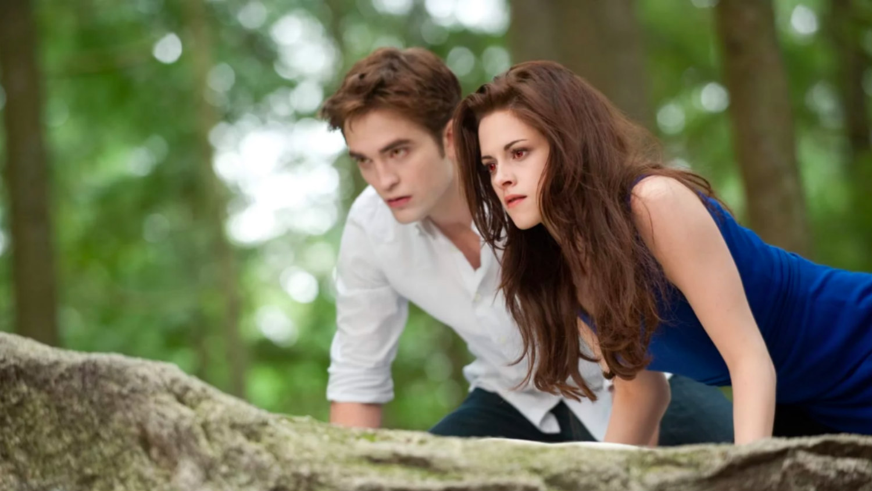 Robert Pattinson, a pale white man wearing a blue shirt, crouches beside Kristen Stewart, a pale white, thin woman with shoulder-length brown hair, on a rock in The Twilight Saga: Breaking Dawn – Part 2