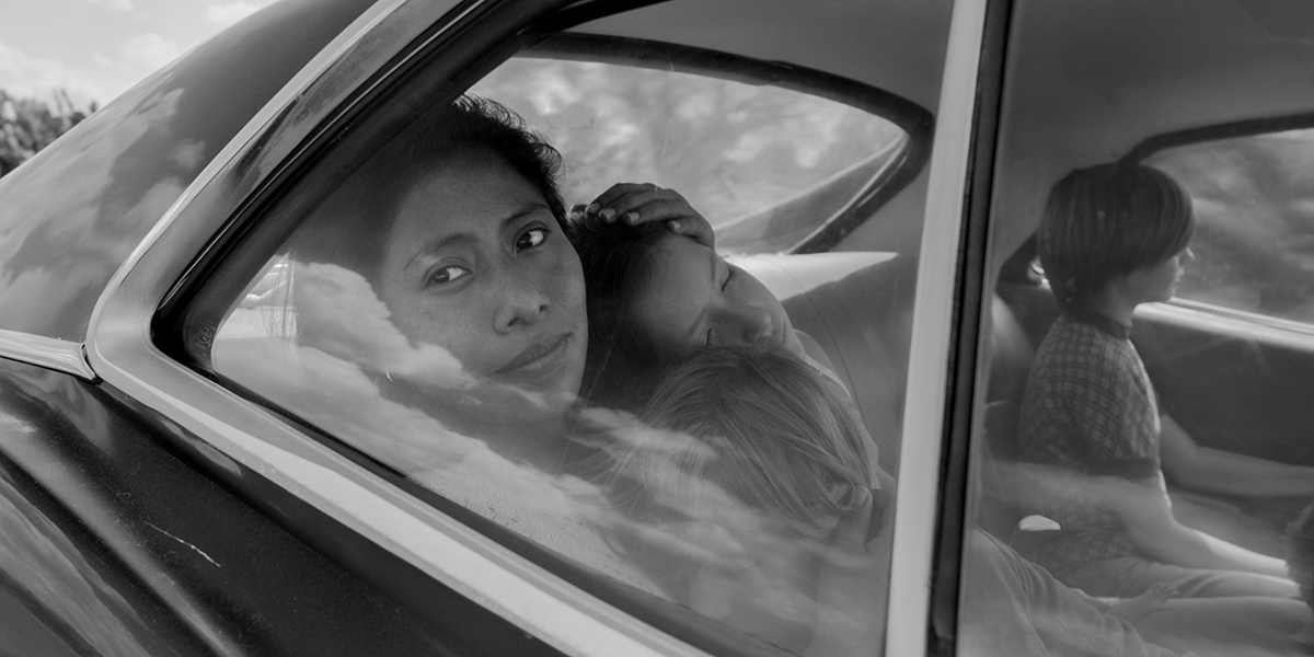 A black and white still of Yalitza Aparicio staring out a car window while holding two children lovingly