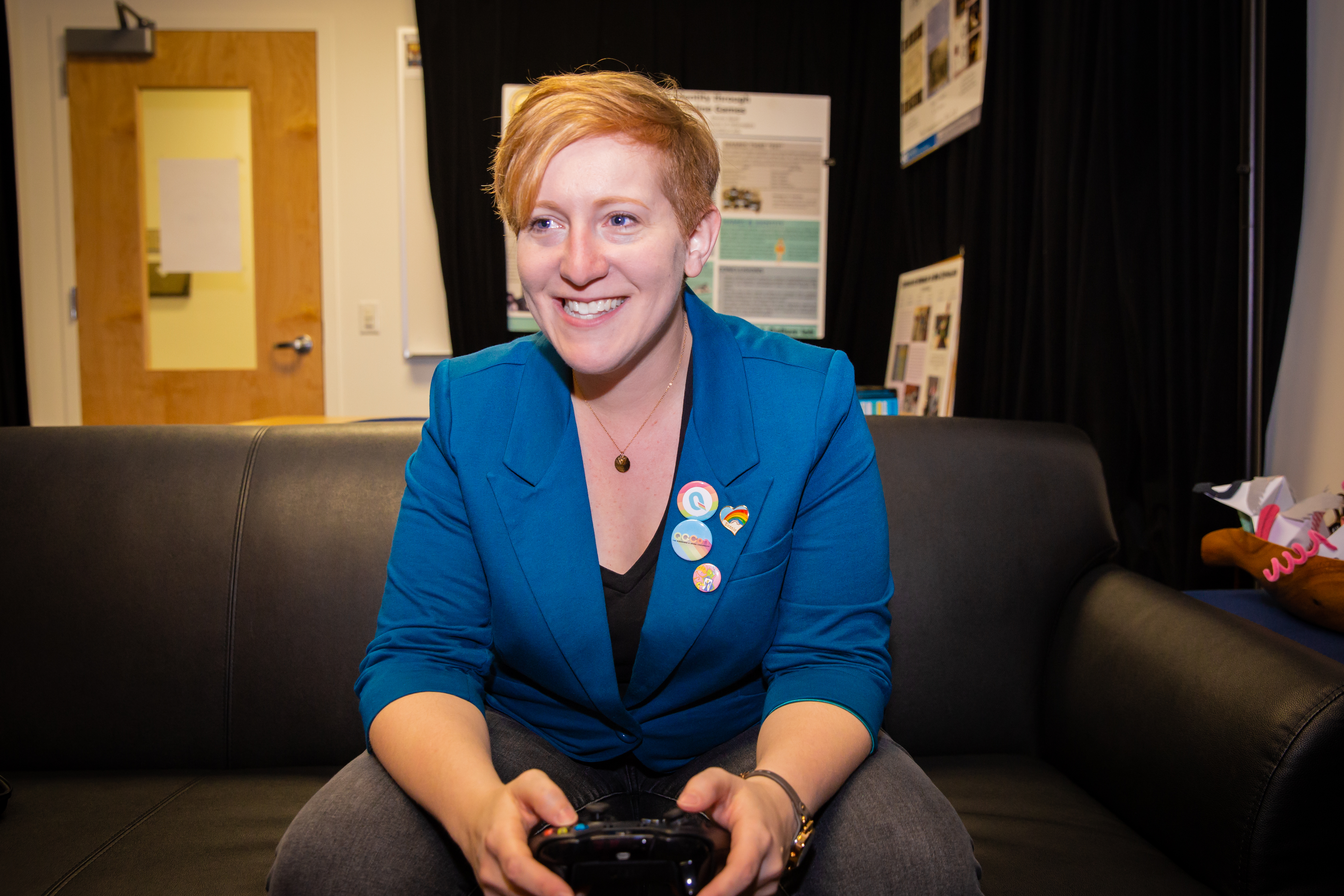 Bonnie Ruberg, a white professor with short, red hair, and wearing an ocean blue blazer, sits on a couch with a game controller in her hand