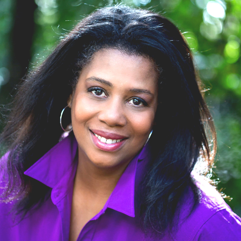 A close-up portrait of a Black woman outside, smiling and wearing a purple blouse