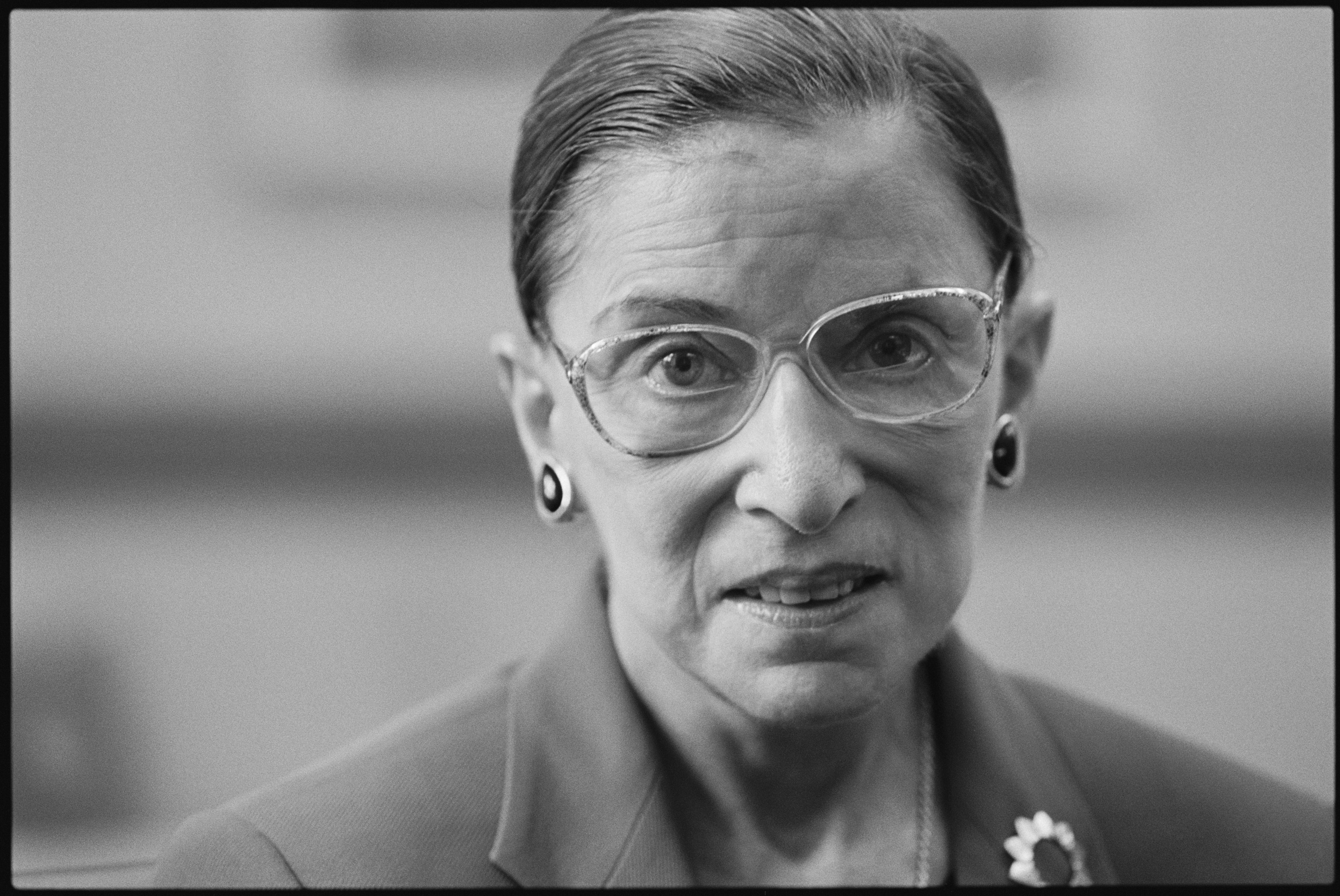 Ruth Bader Ginsburg, a white Jewish woman wearing glasses with her hair pulled back in a bun, smiles for the camera