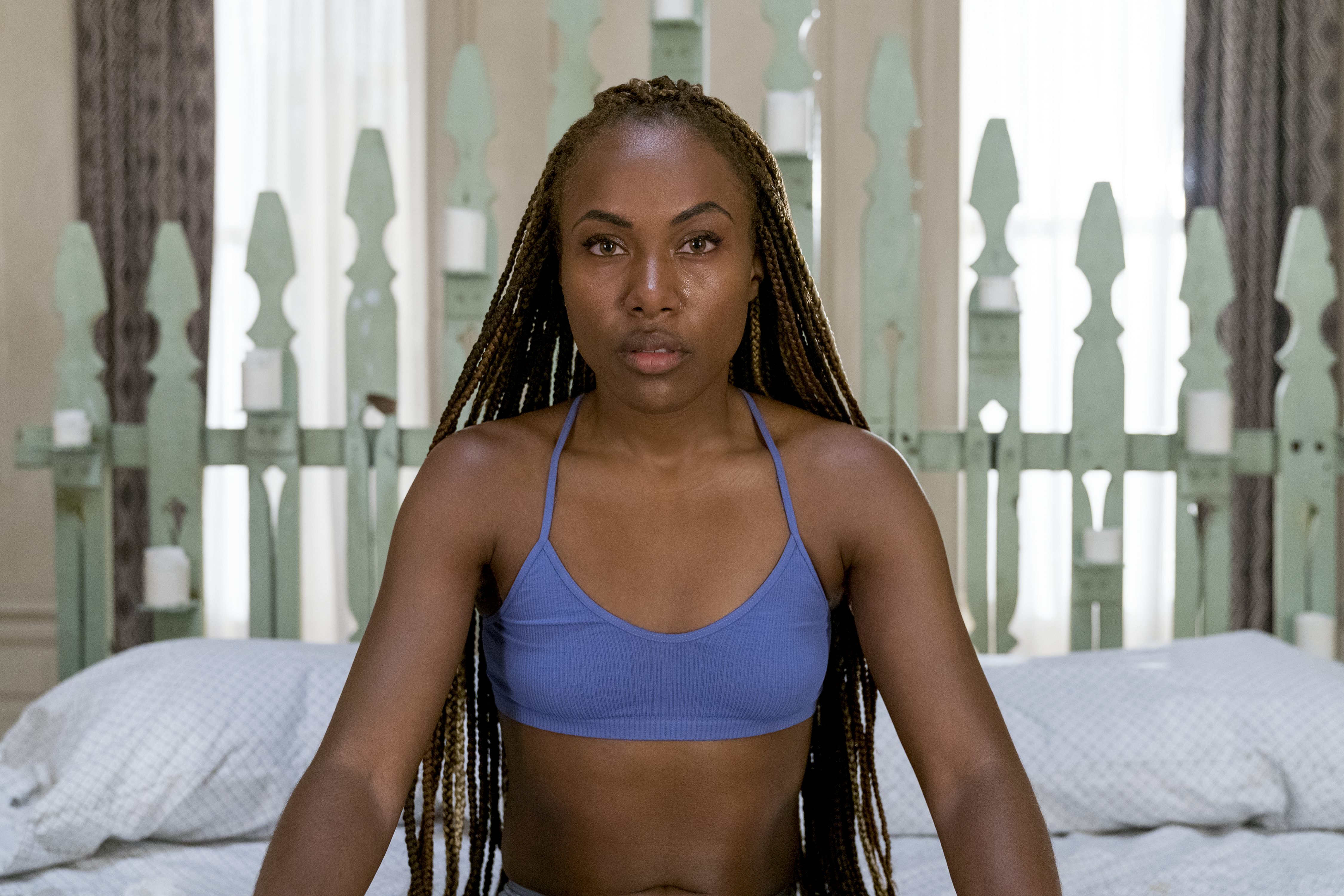 a brownskinned woman with long, brown braids sits on a bed with sad eyes