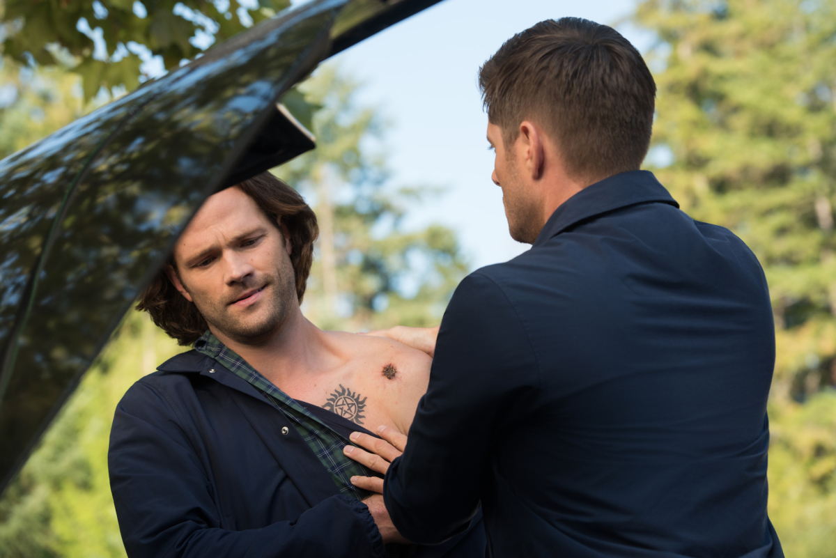 two white men in their 30s stand in front of a car on Supernatural