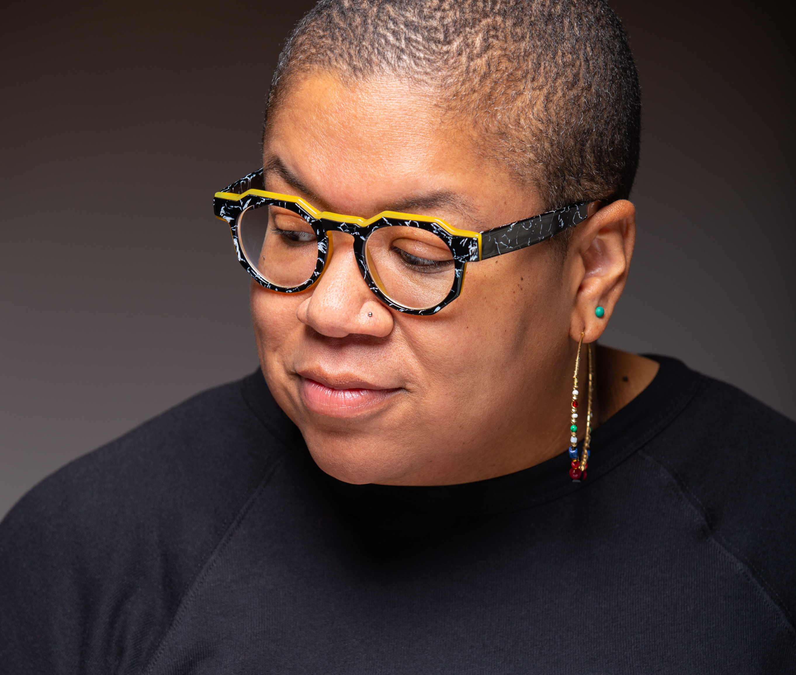 Samantha Irby, a Black woman with cropped hair, wears artful glasses with yellow detailing and a black t-shirt and looks away from the camera.