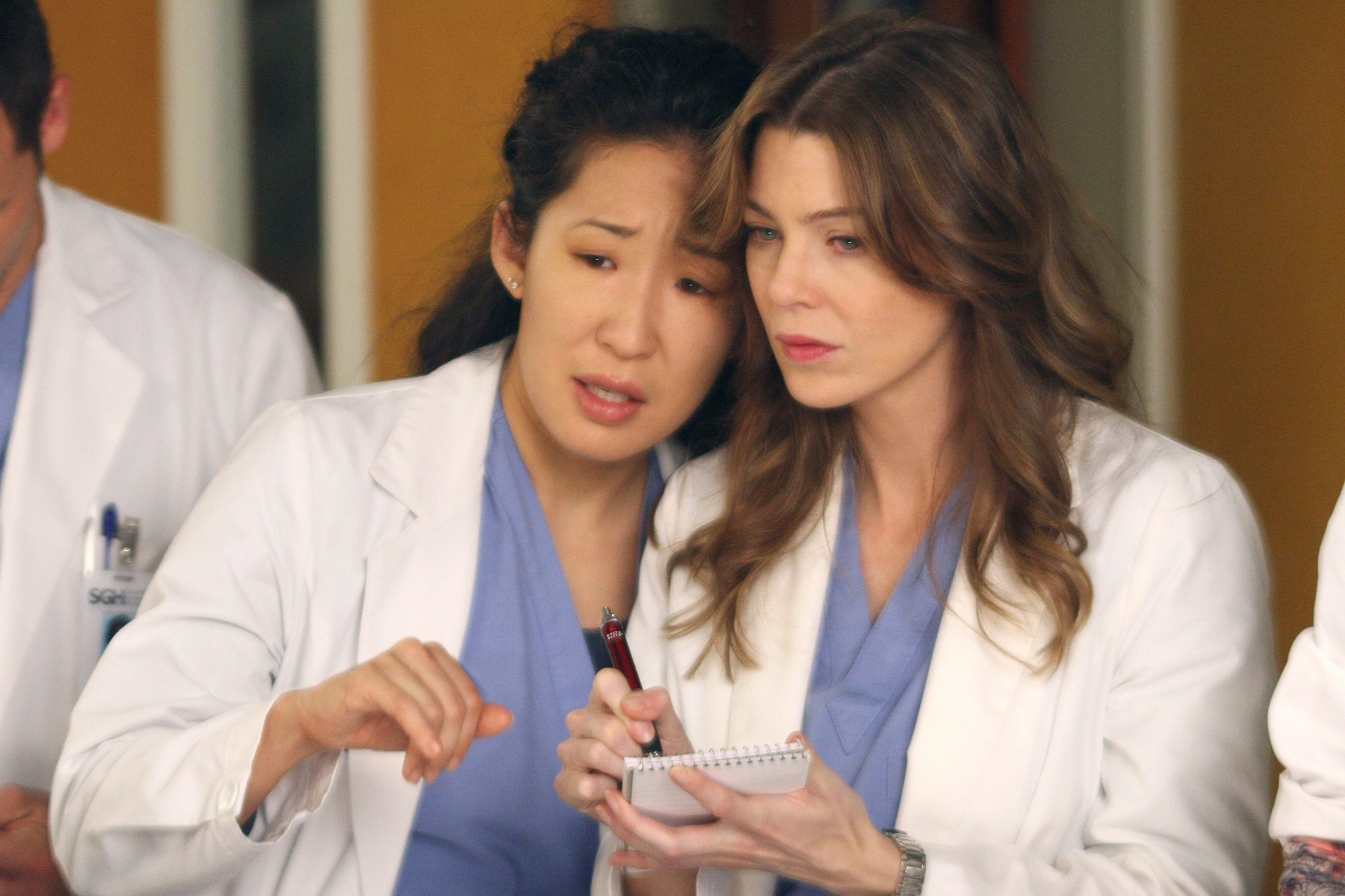 Sandra Oh plays Cristina Yang, an Asian American woman with curly black hair and wearing scrubs, stands beside Ellen Pompeo playing Meredith Grey, a white woman also wearing scrubs in Grey's Anatomy