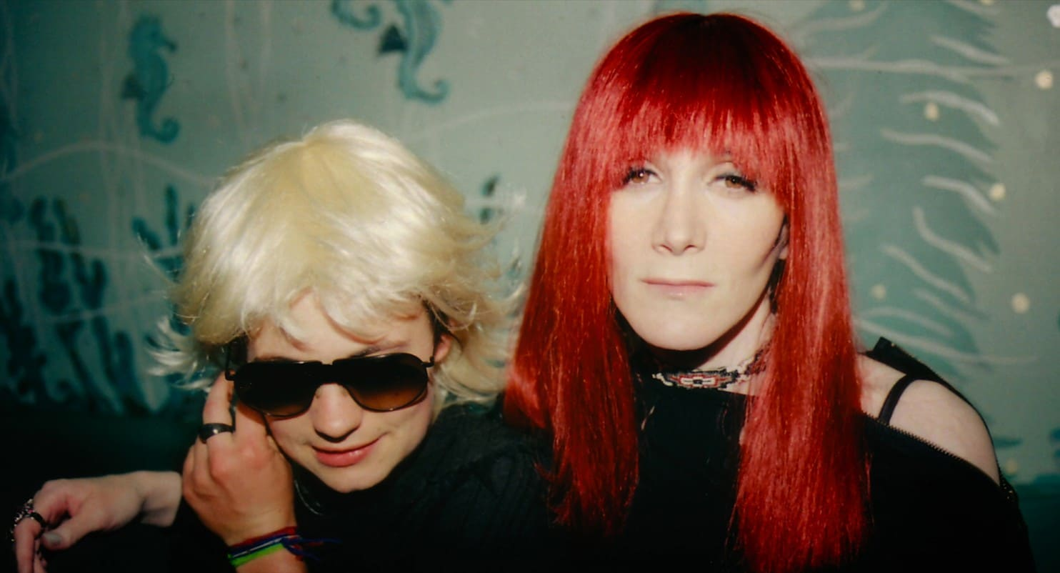 a white person with short, blonde hair stands beside a white woman with red, shoulder-length hair