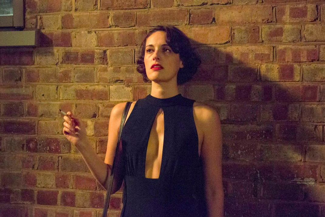 Phoebe Waller-Bridge as Fleabag, a white woman standing against a brick wall smoking a cigarette in a black jumpsuit with a low cutout in the chest