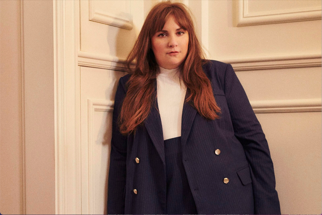 Lena Dunham, a white woman with shoulder-length brown hair, poses in a navy blue blazer against a cream-colored wall