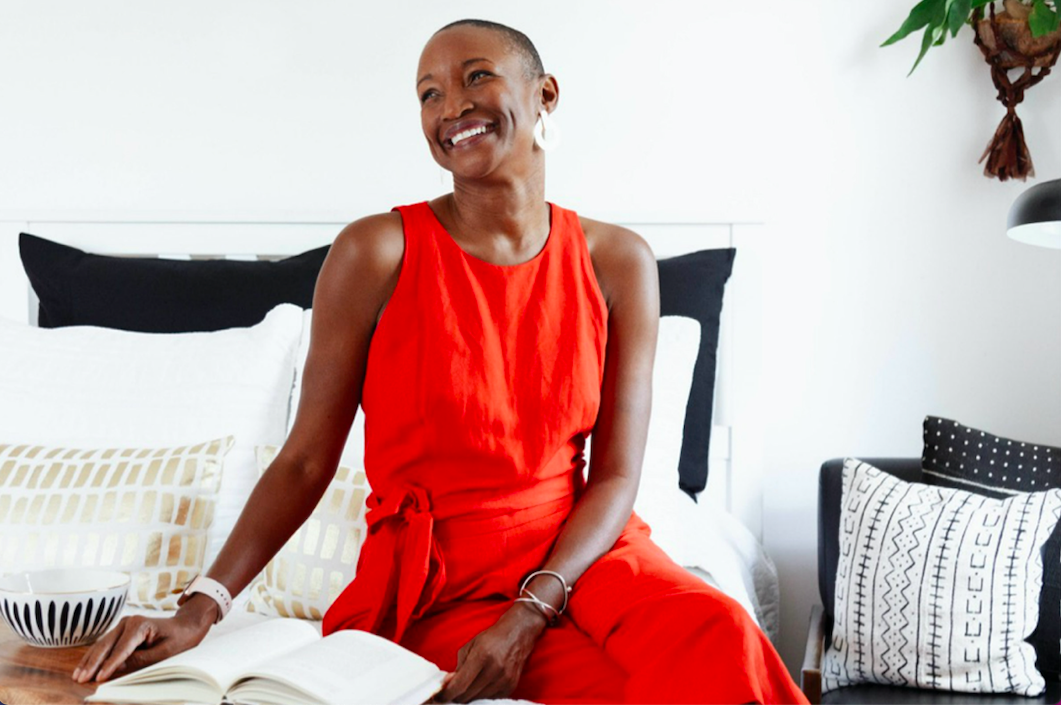 Gabrielle Platt, a Black woman with a caesar cut, sits on a white and black comforter in a red dress and smiles