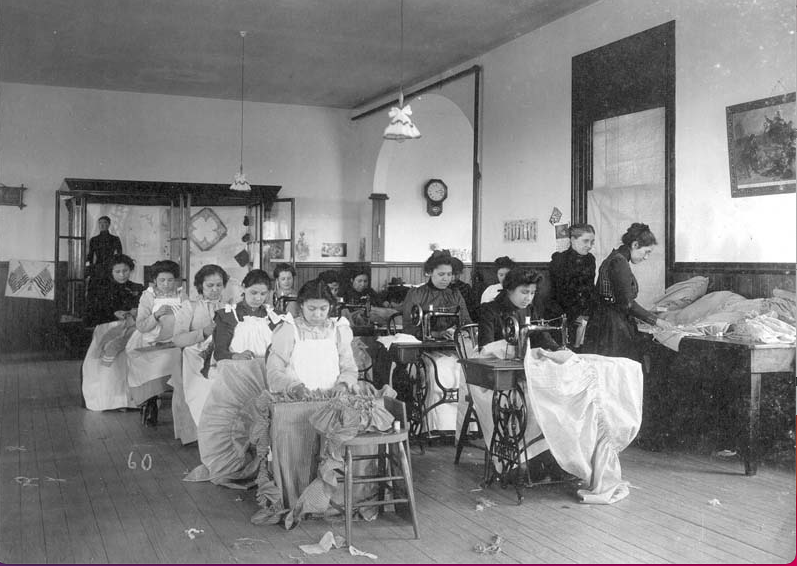 a group of Indigenous students, all wearing dresses, sit behind sewing machines at the Carlisle Indian School