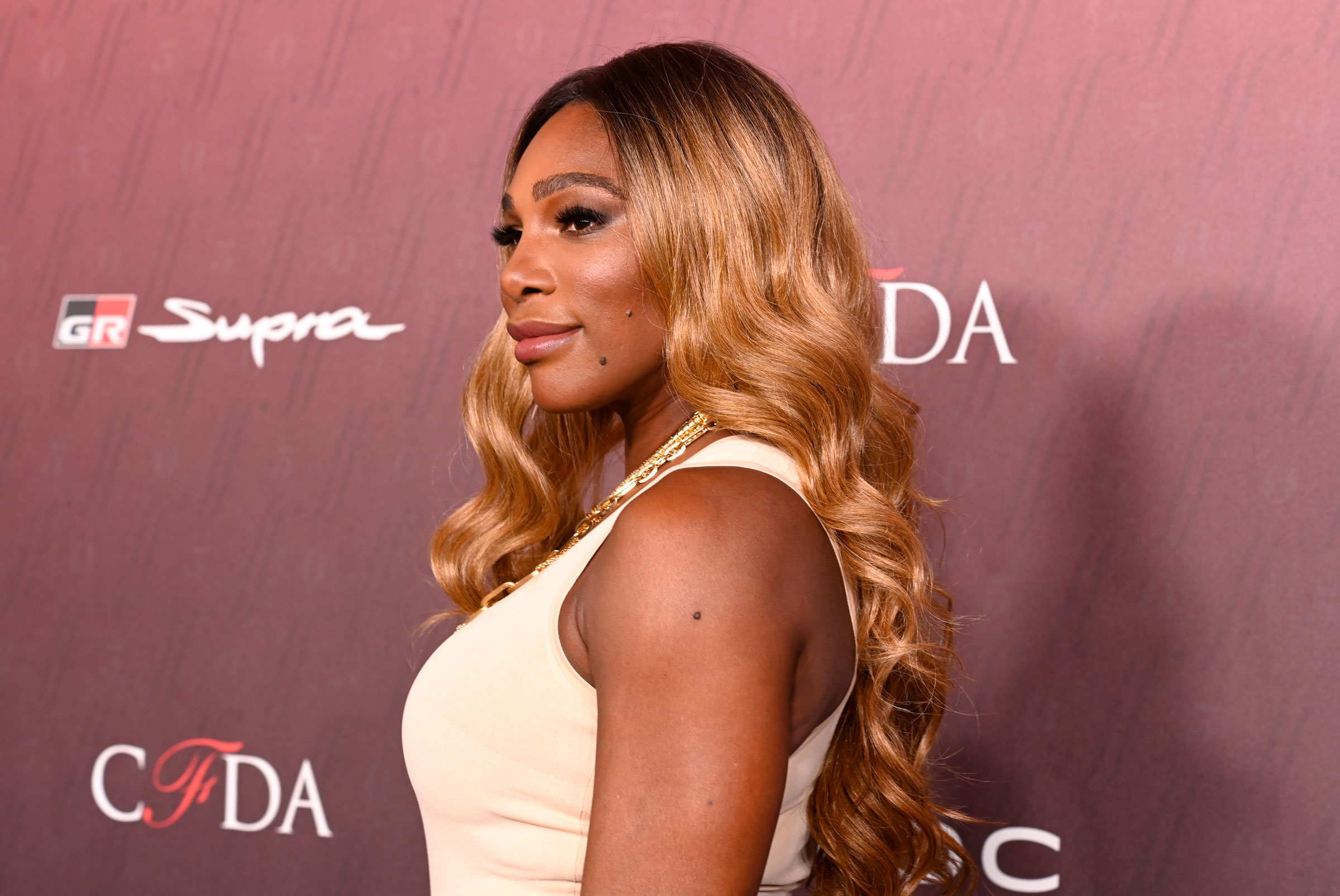 Serena Williams, a dark-skinned Black woman wearing blond, curly hair, poses on a red carpet