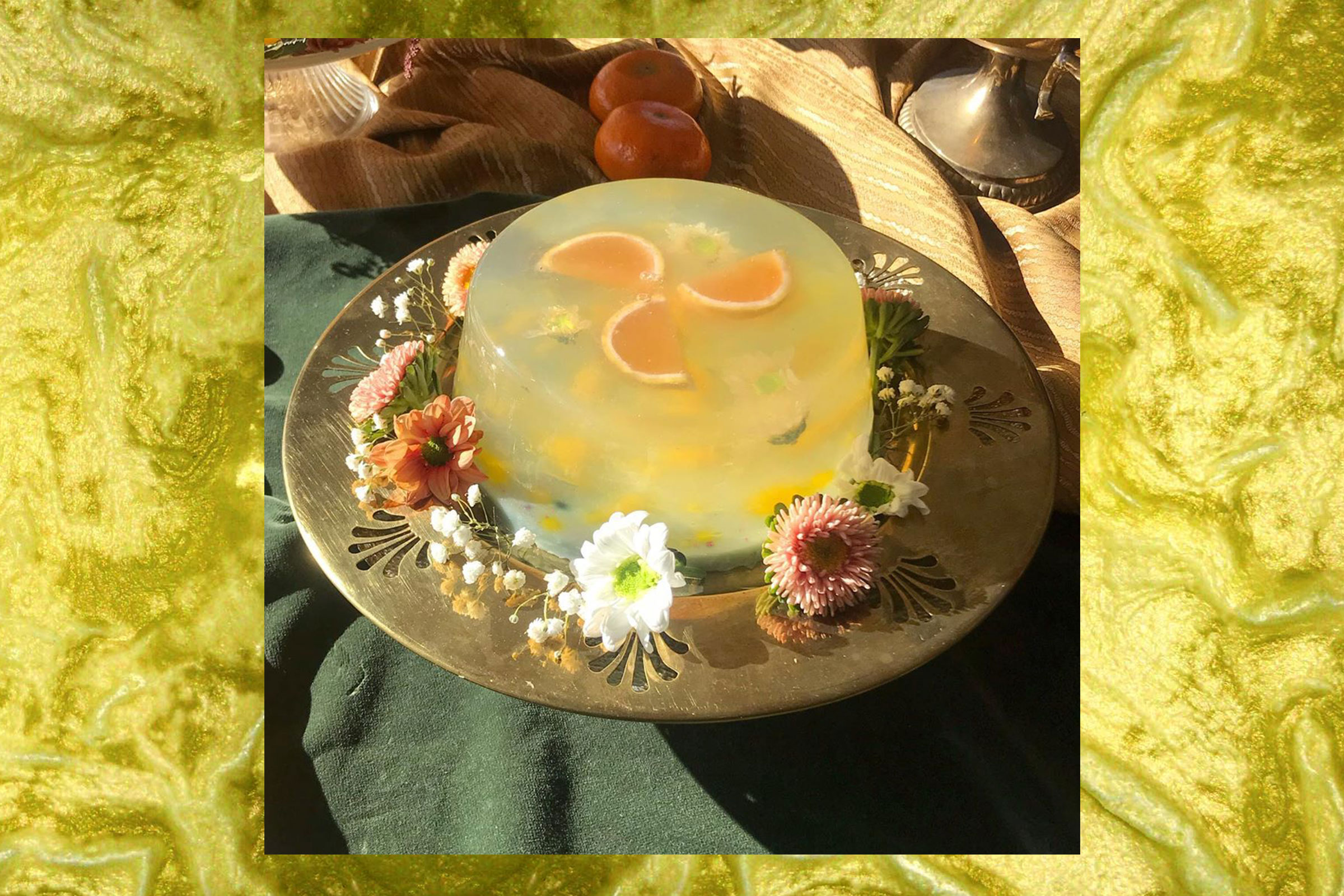 One of Sharona Franklin's edible jelly sculptures. Slices of citrus fruit are visible near the top of the jelly, and the jelly itself is surrounded by an assortment of flowers.