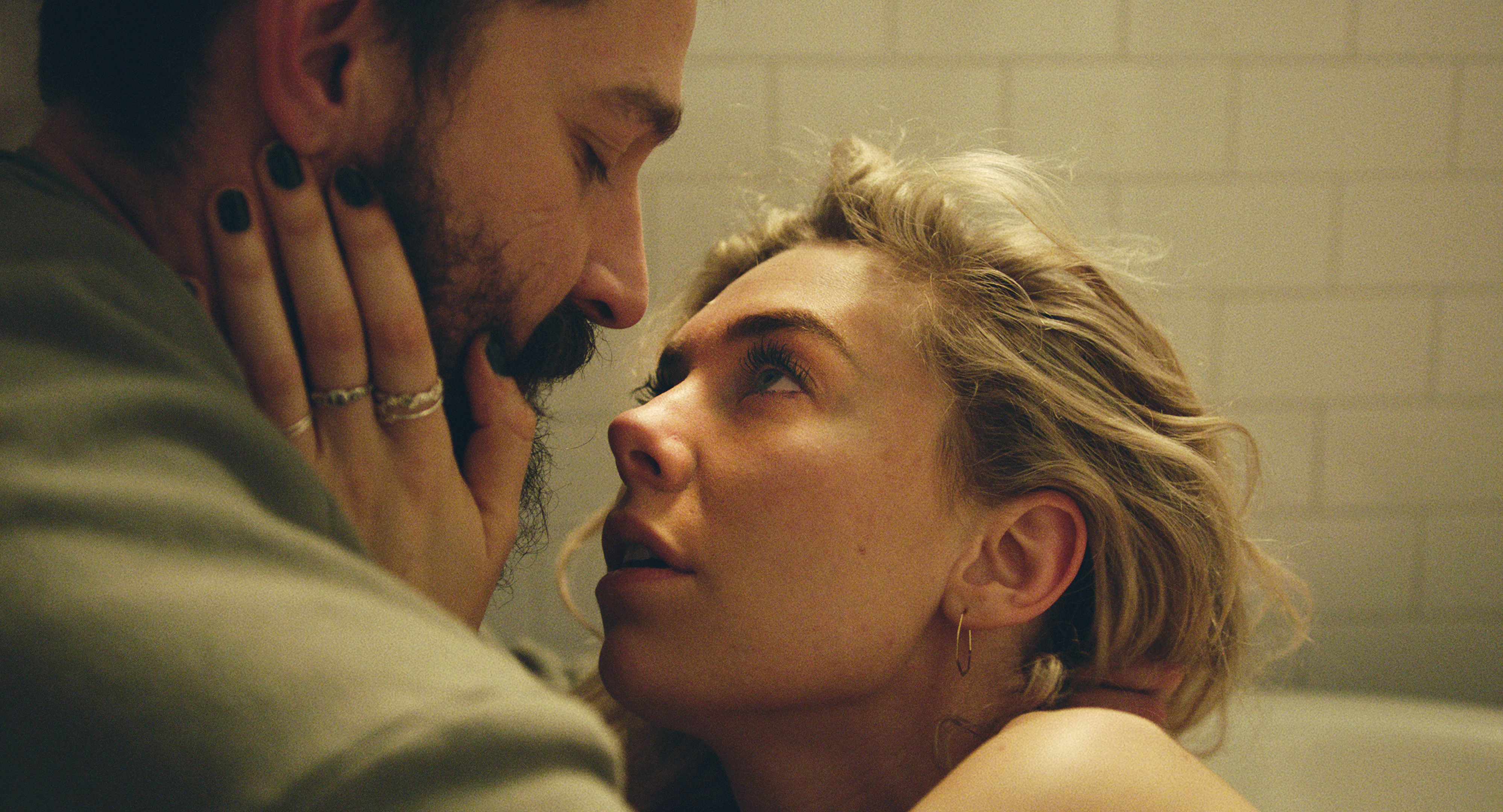 a close-up shot of Vanessa Kirby, a white woman, holding Shia LeBeouf, a bearded white man's face in her hands in Pieces of a Woman
