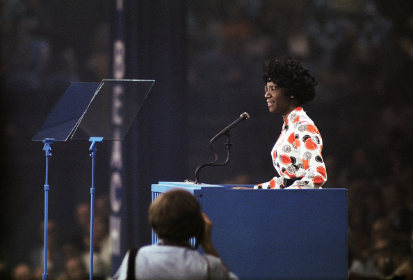 Shirley Chisholm, a Black woman with a short, black afro, stands behind a podium in an orange and white blouse