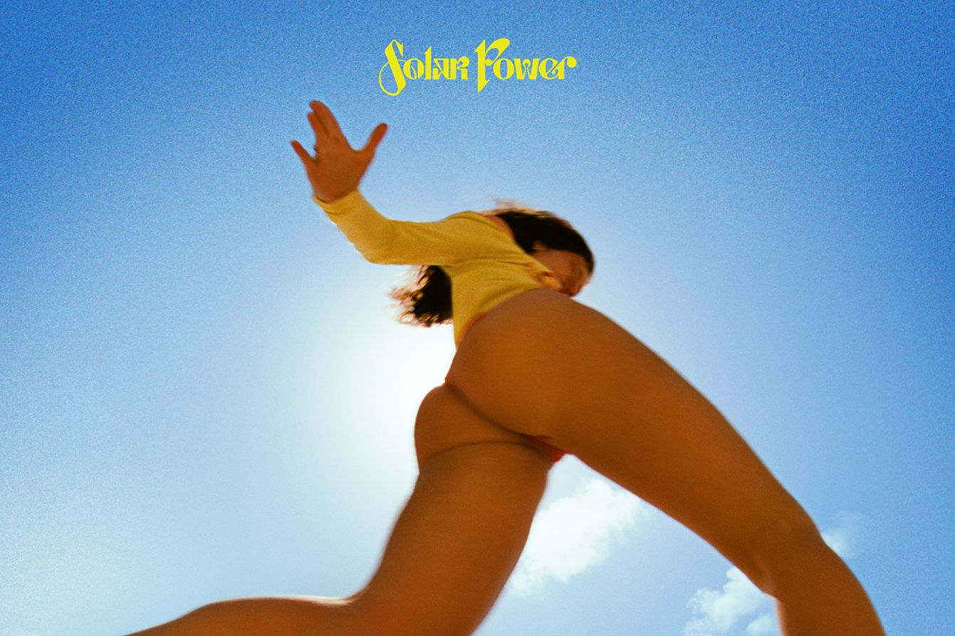 Lorde, a thin, white woman is shown from below in a yellow body suit on the cover of Solar Power
