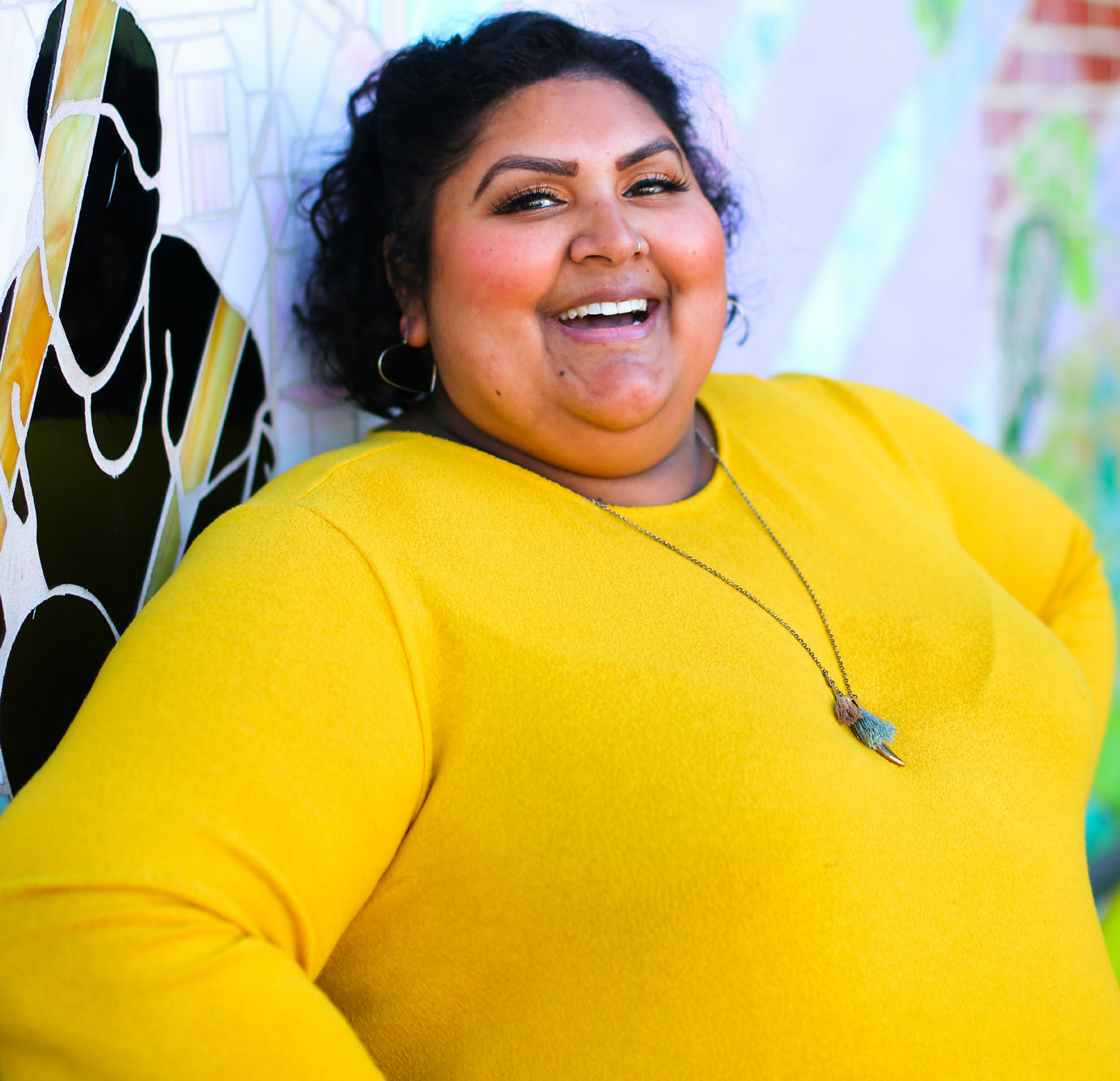 a plus-size person wearing a yellow shirt smiles brightly at the camera