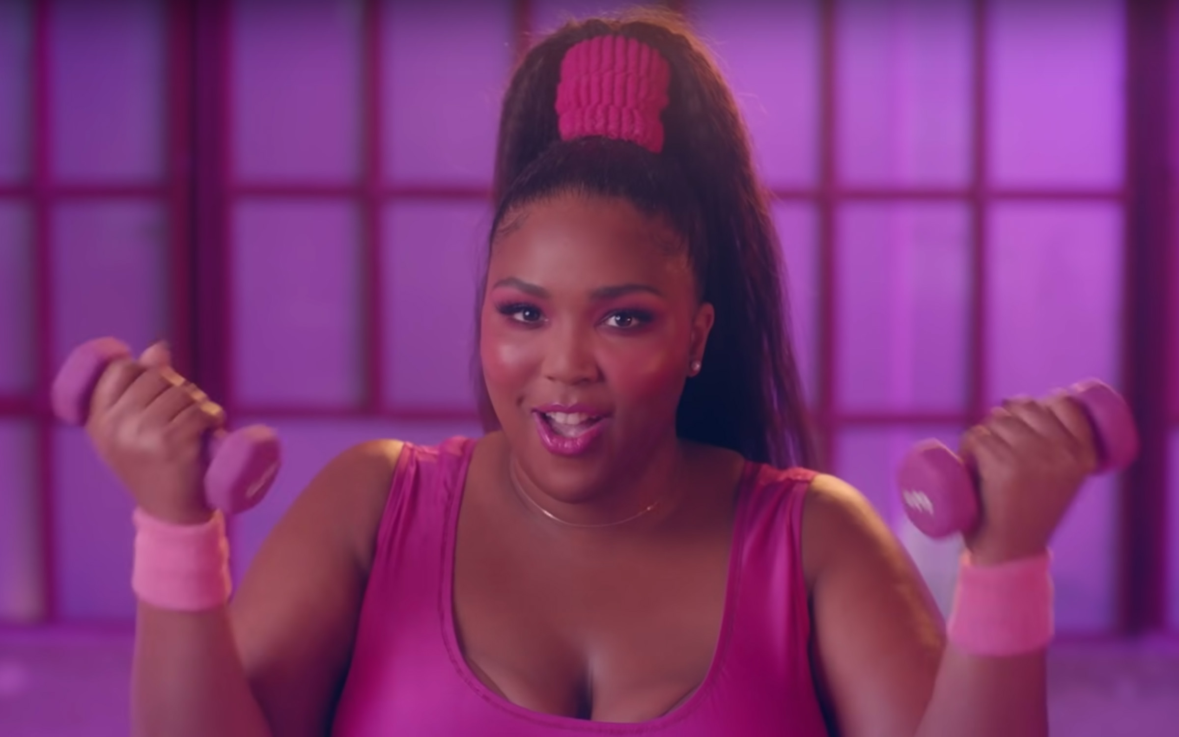 Lizzo, a plus-size Black woman musician, wears a high ponytail with a pink aerobic jumpsuit, in the Juice video