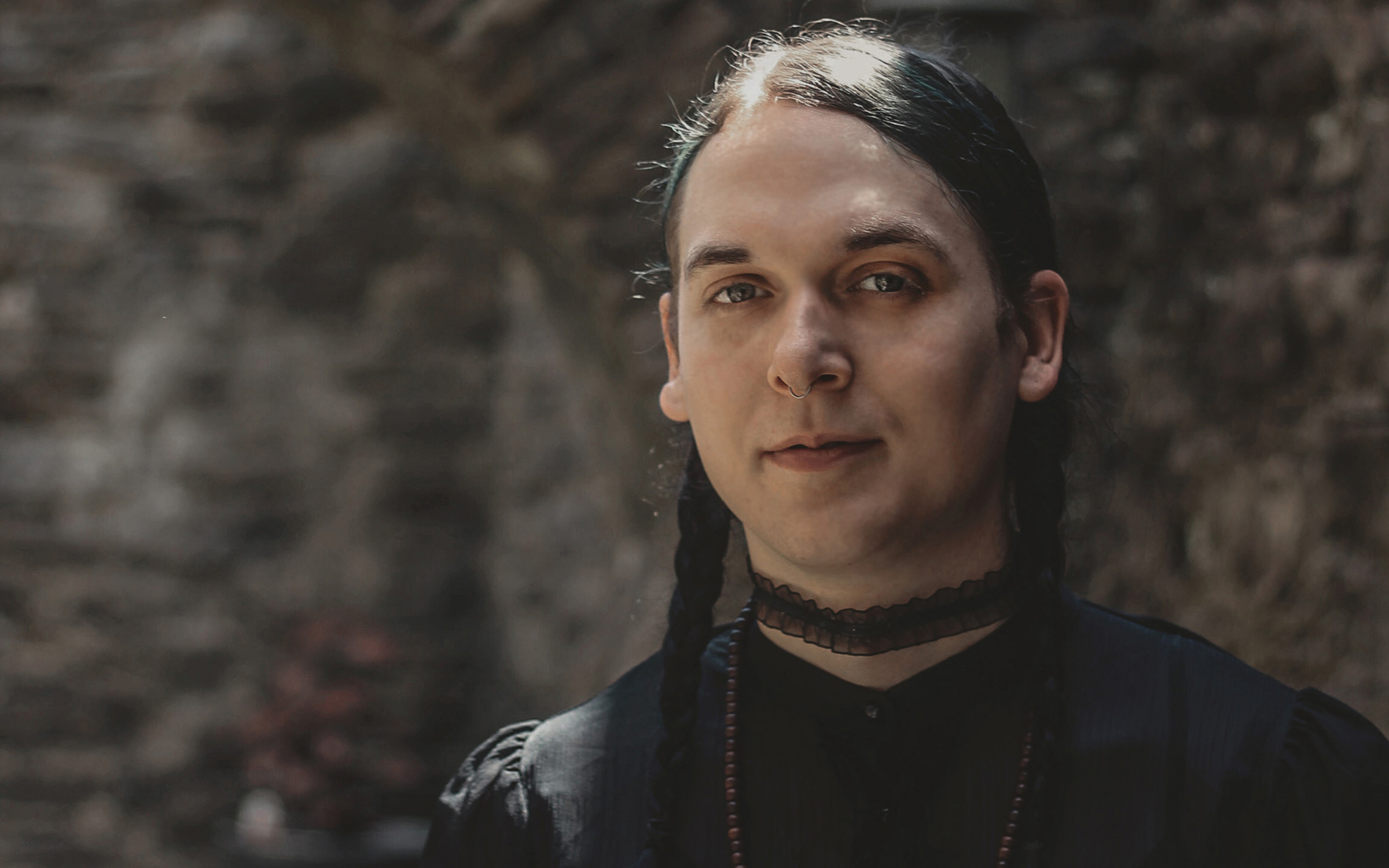portrait of author and chef, Stacy Jane Grover, a white trans woman with braided hair, wearing a black blouse and a long beaded necklace standing in front of a stone archway