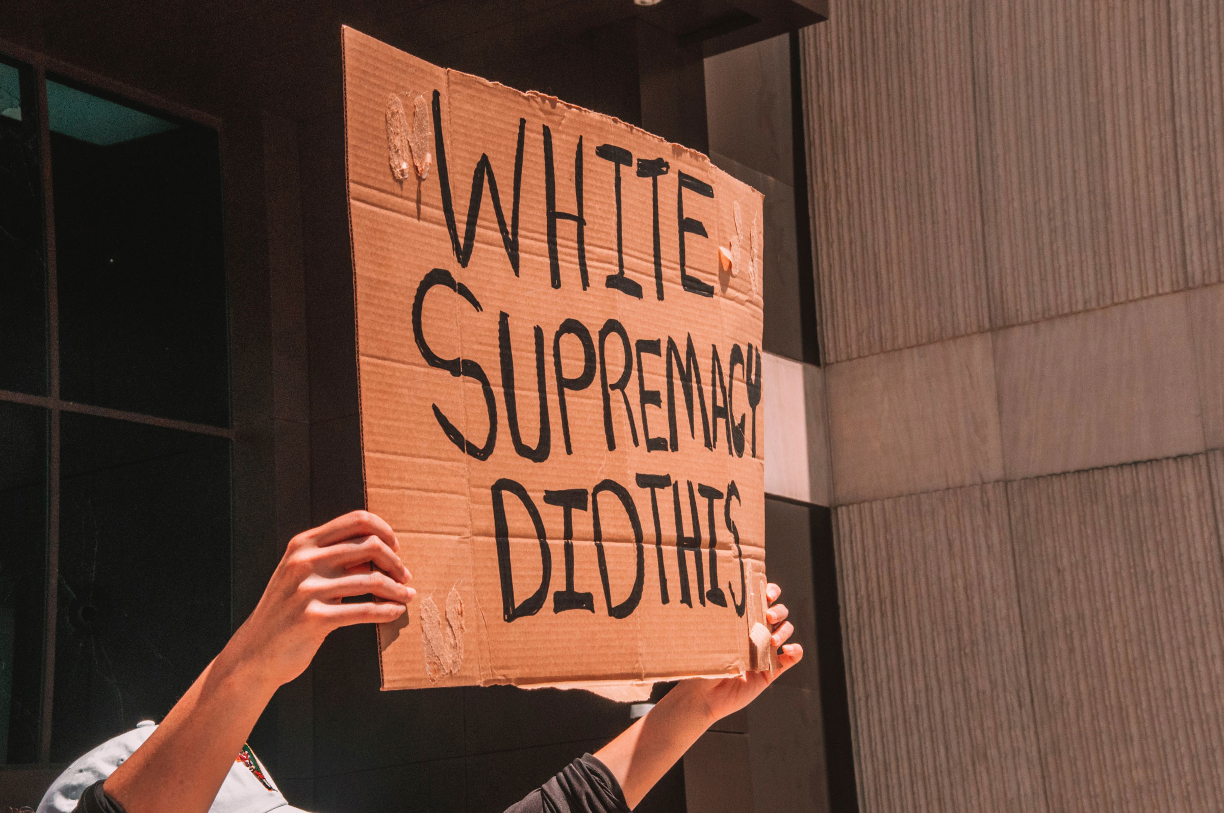 """A protest sign reading """"White supremacy did this."""""""