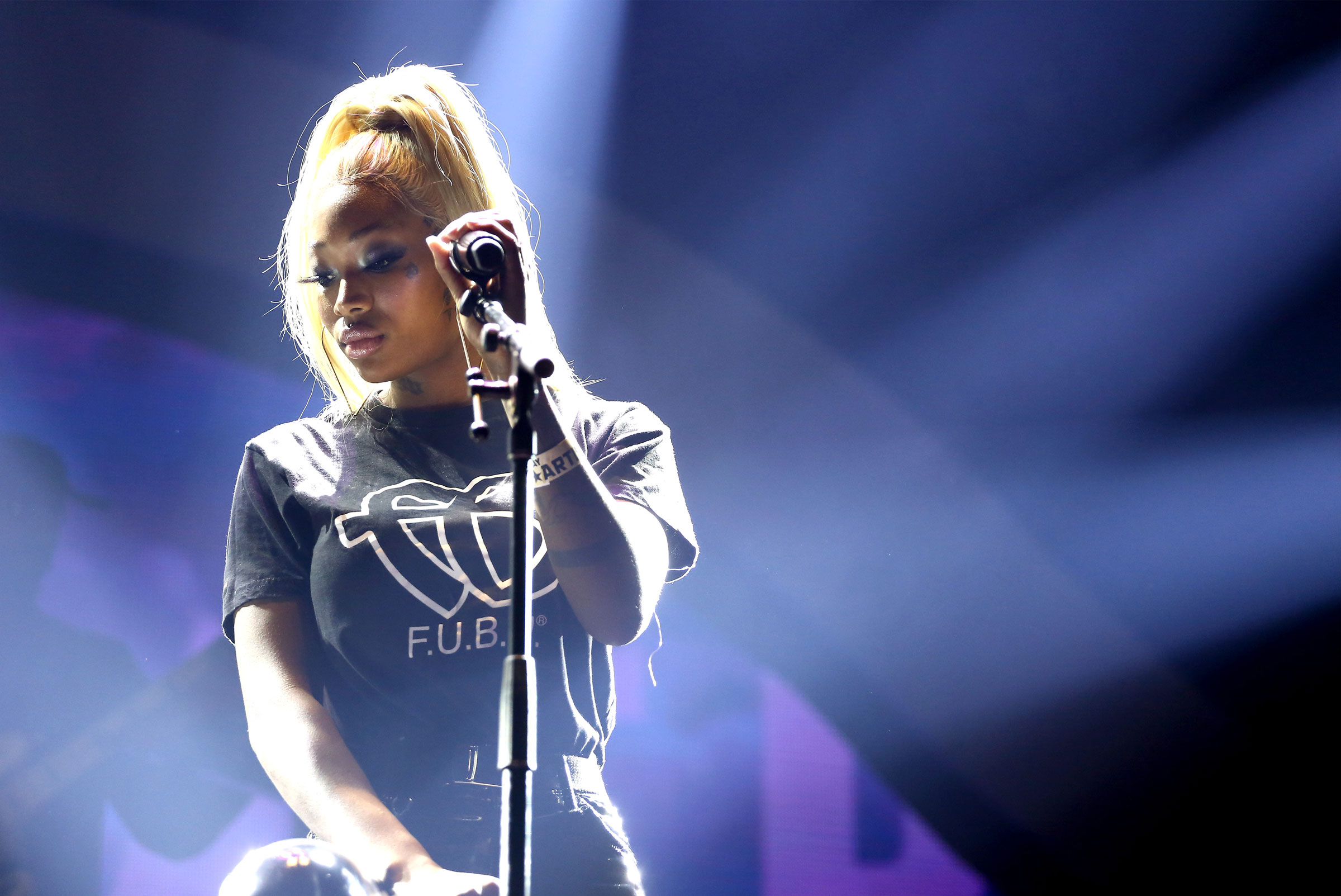 Summer walker, a young Black woman, sings on stage. Her hair is in a long blond ponytail and she wears a t-shirt.