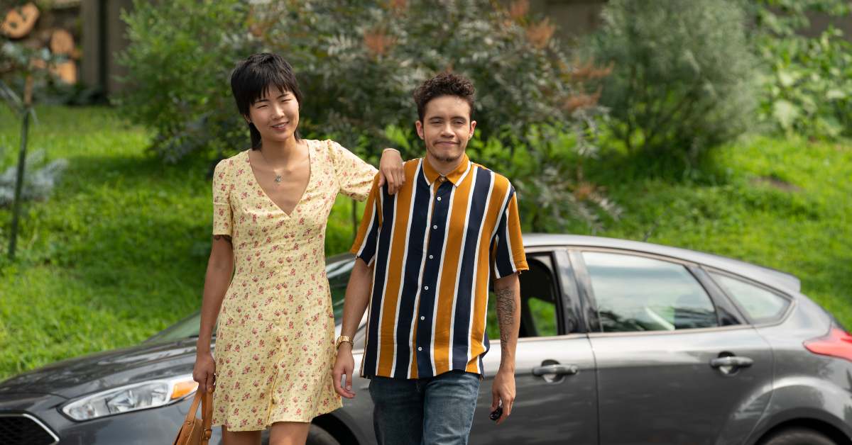 A photo of Tales of the City May Hong and Garcia as Margot, an Asian-American lesbian, and Jake, a Latinx trans man.