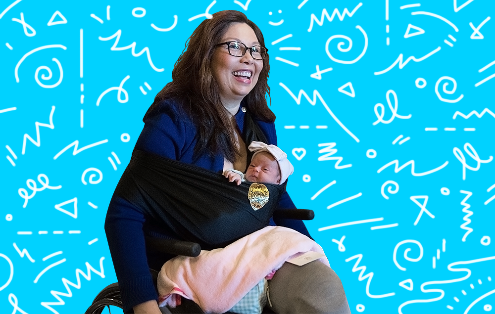 Tammy Duckworth in her wheelchair holding her daughter