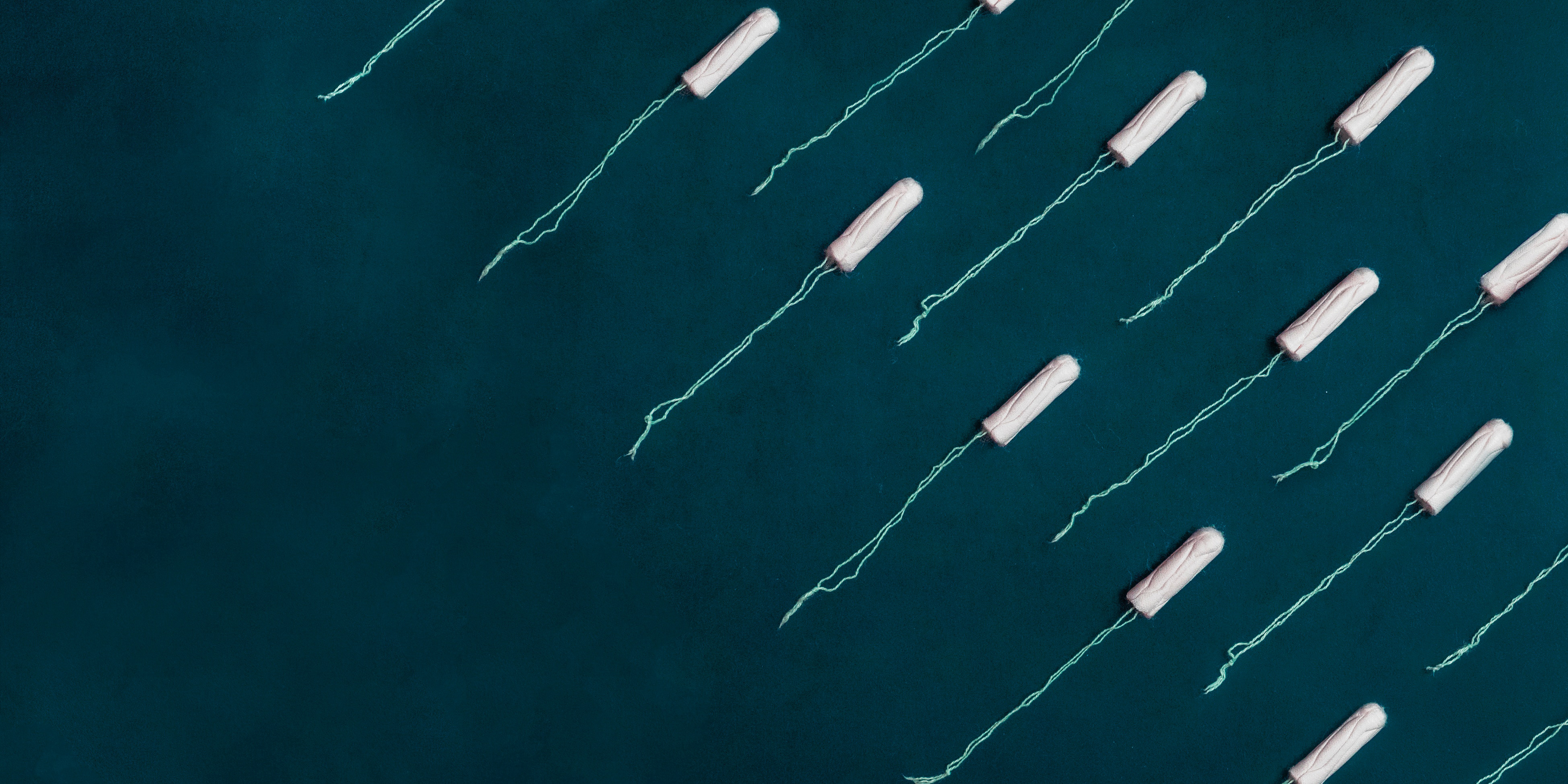 Unwrapped tampons arranged in rows against a teal background