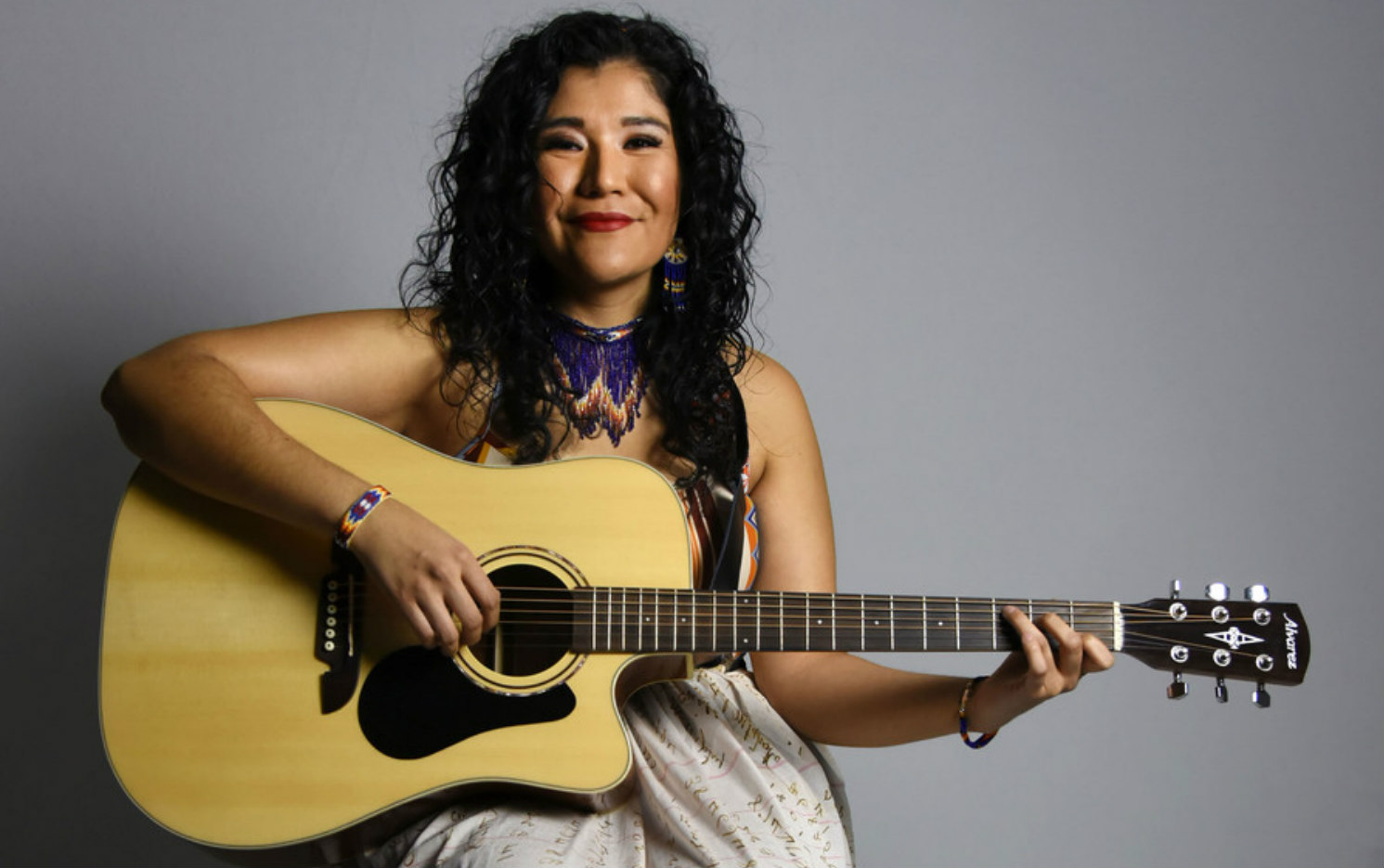 Photo of Tanaya Winder, a Black Indigenous musician and artist, wearing a tiered beaded necklace, sitting and smiling while holder her guitar