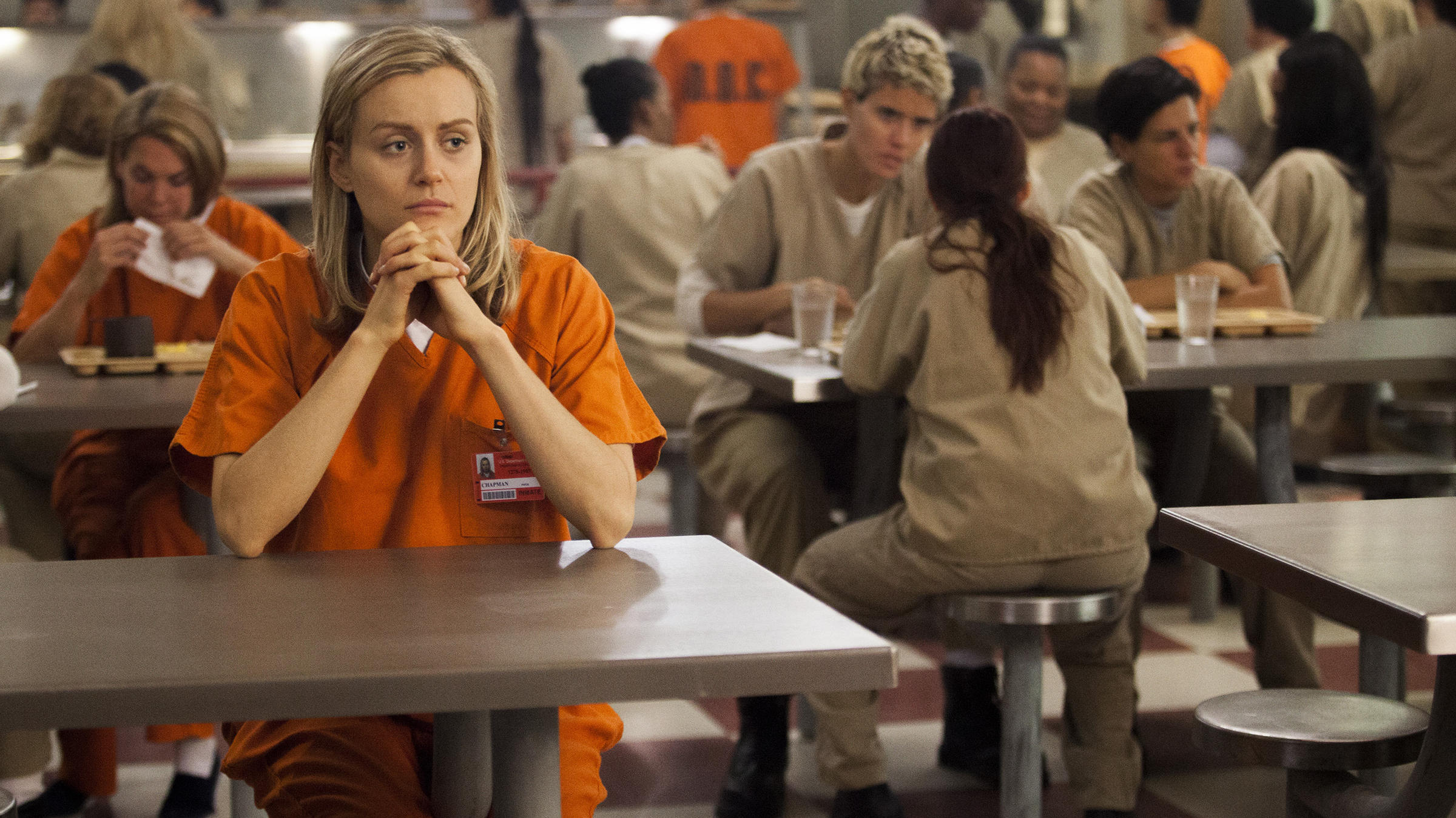 a white woman with shoulder-length blonde hair sits in an orange jumpsuit in a prison cafeteria on Orange is the New Black