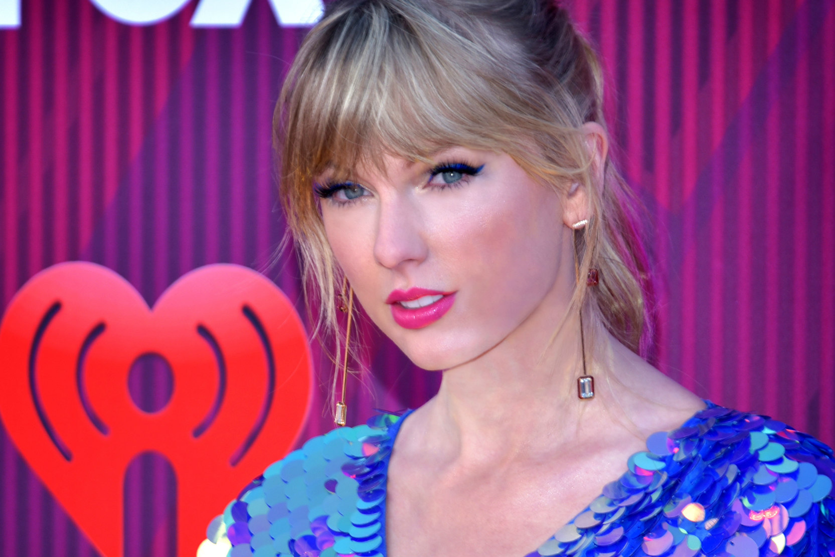 Taylor Swift, a white woman with blond bangs and pink lipstick, poses on a red carpet