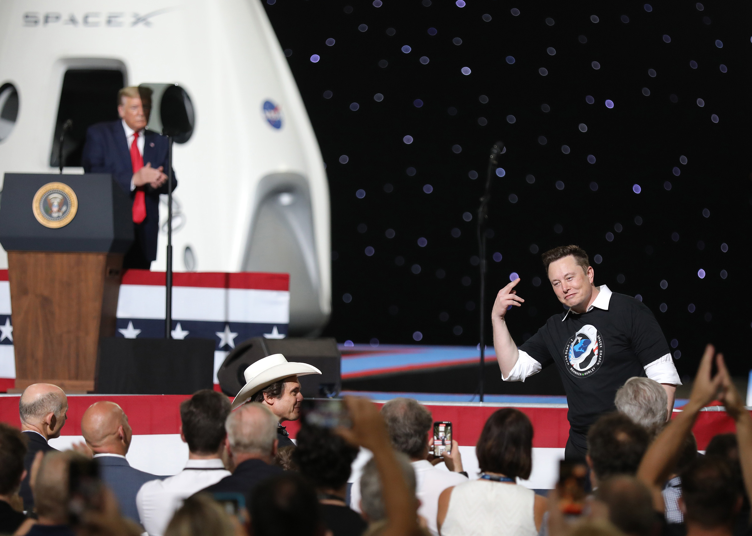 Donald Trump and Elon Musk, two white men, stand together on a stage in front of a white SpaceX vessel