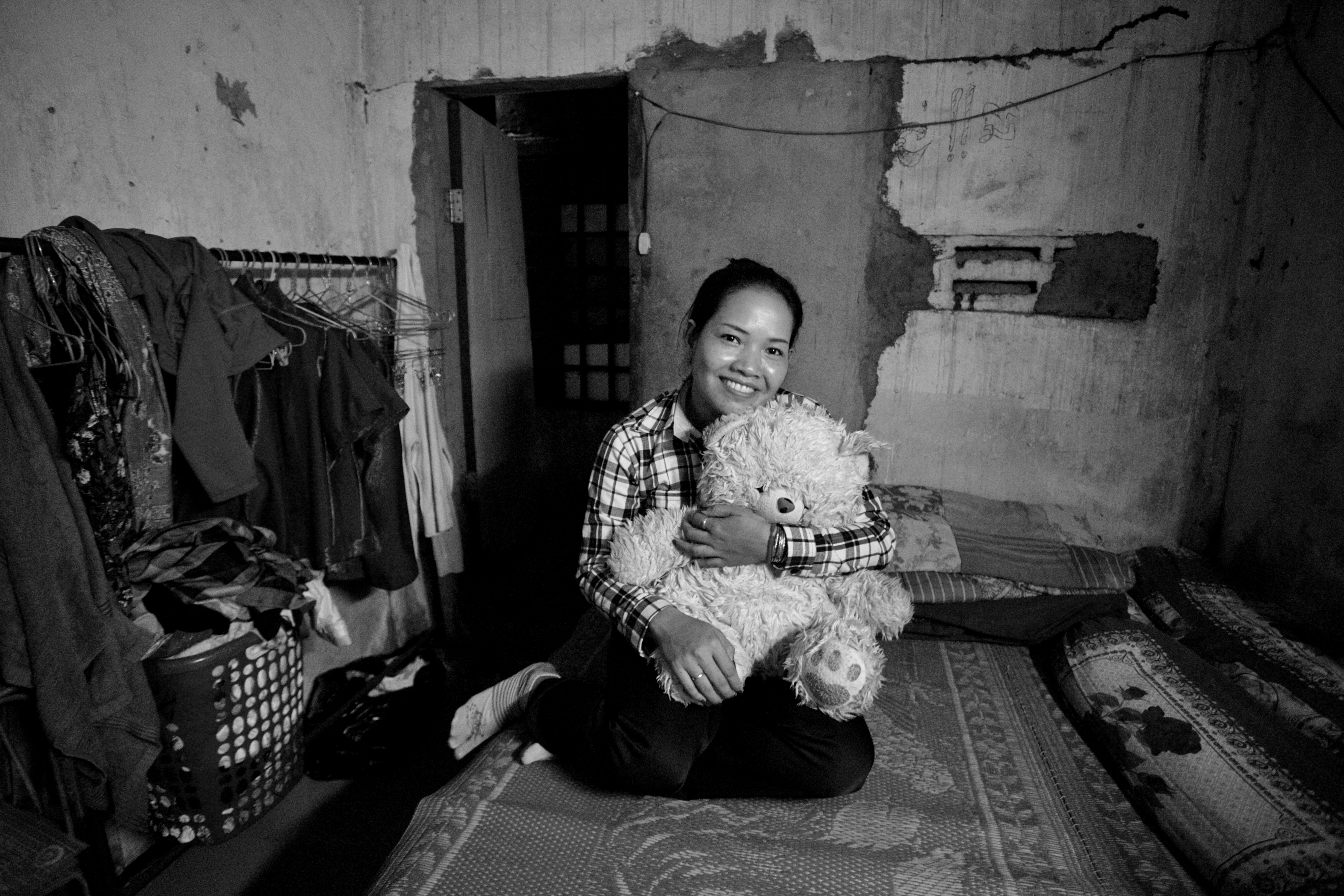 Tep Sareoung, a Cambodian laborer, poses on the floor while holding a white, fluffy dog