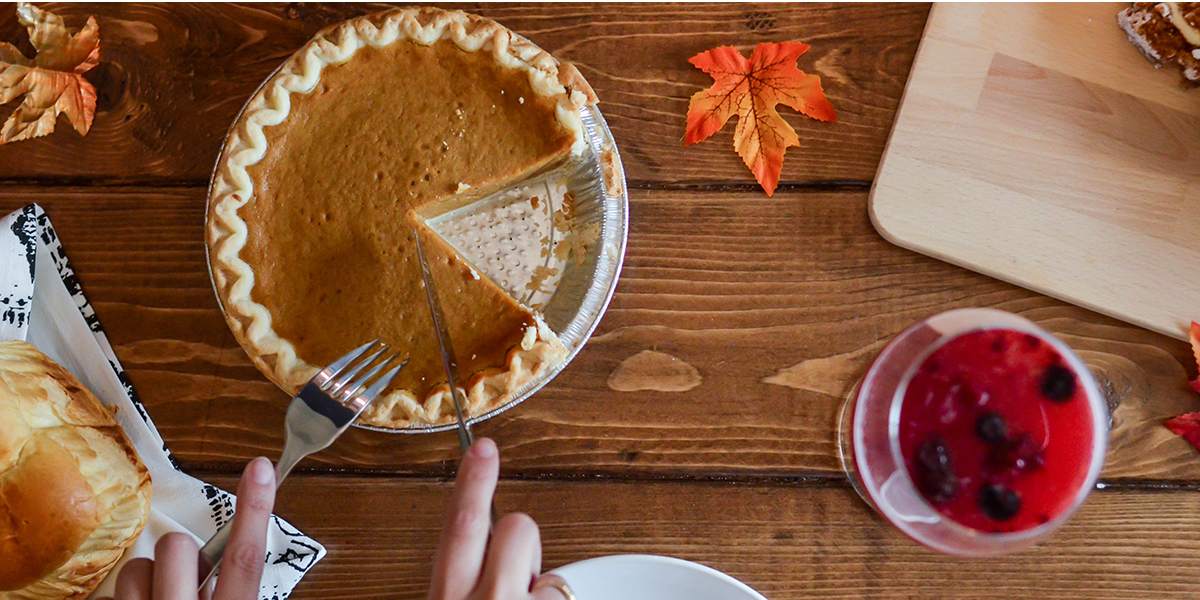 Birds eye view of a Thanksgiving dinner spread as a pair of hands cut into a pumpkin pie