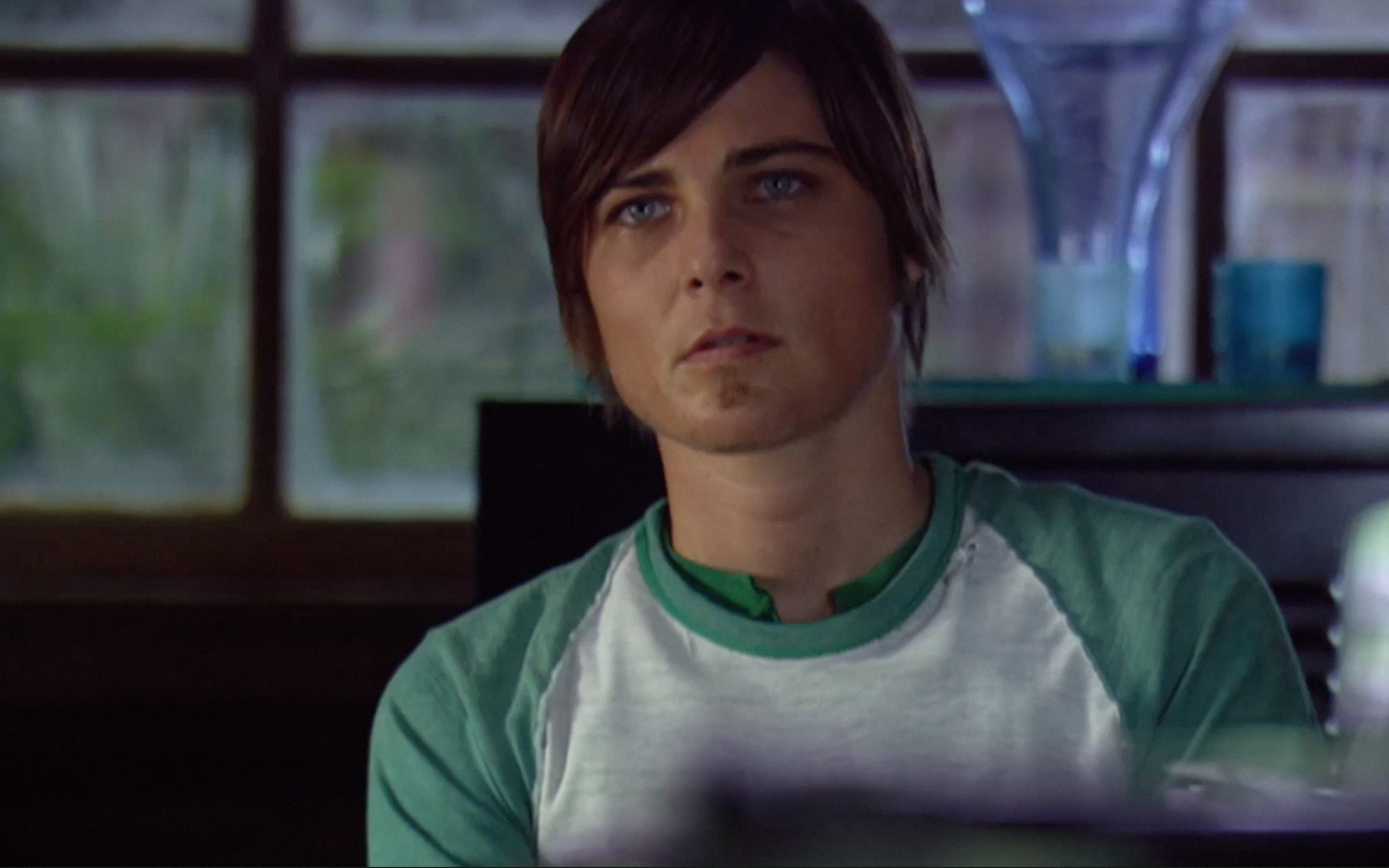 A photo of Max from The L Word, a white person with brown hair and blue eyes. Max looks into the camera.