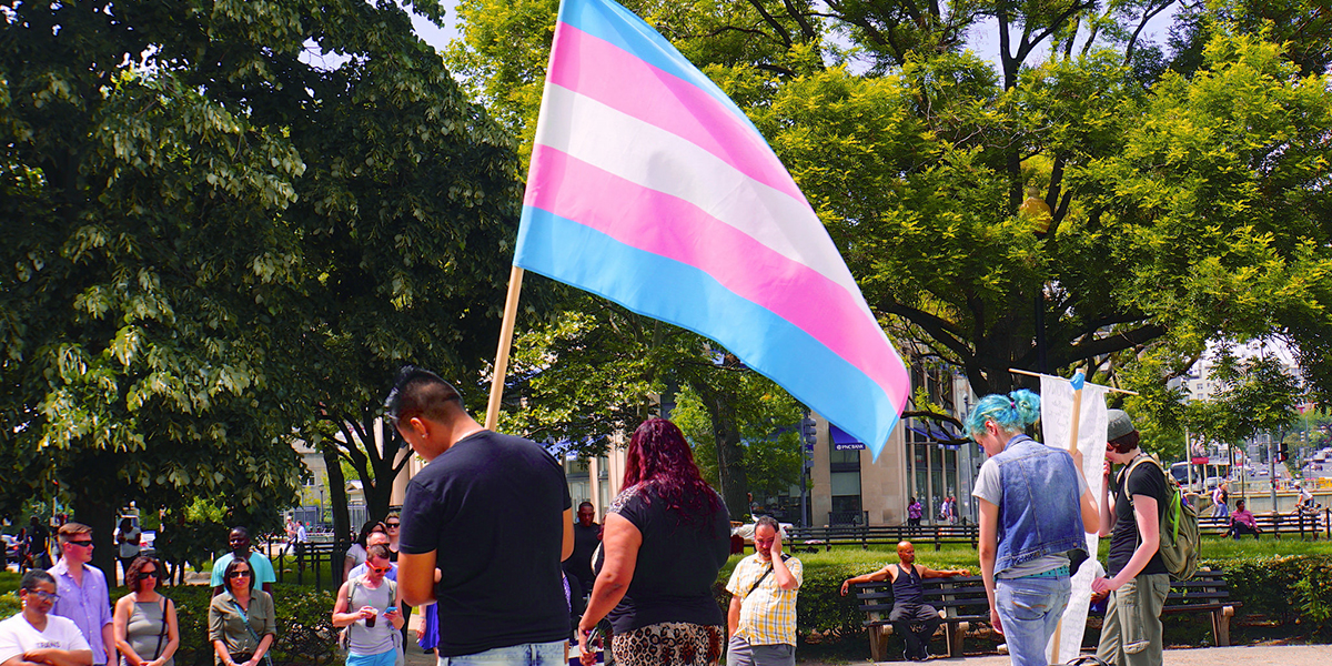 A person holds the trans flag at a rally while the crowd bows their heads in solidarity