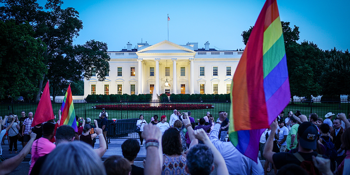 Protesters holding rainbow flags with raised fists in front of the White House