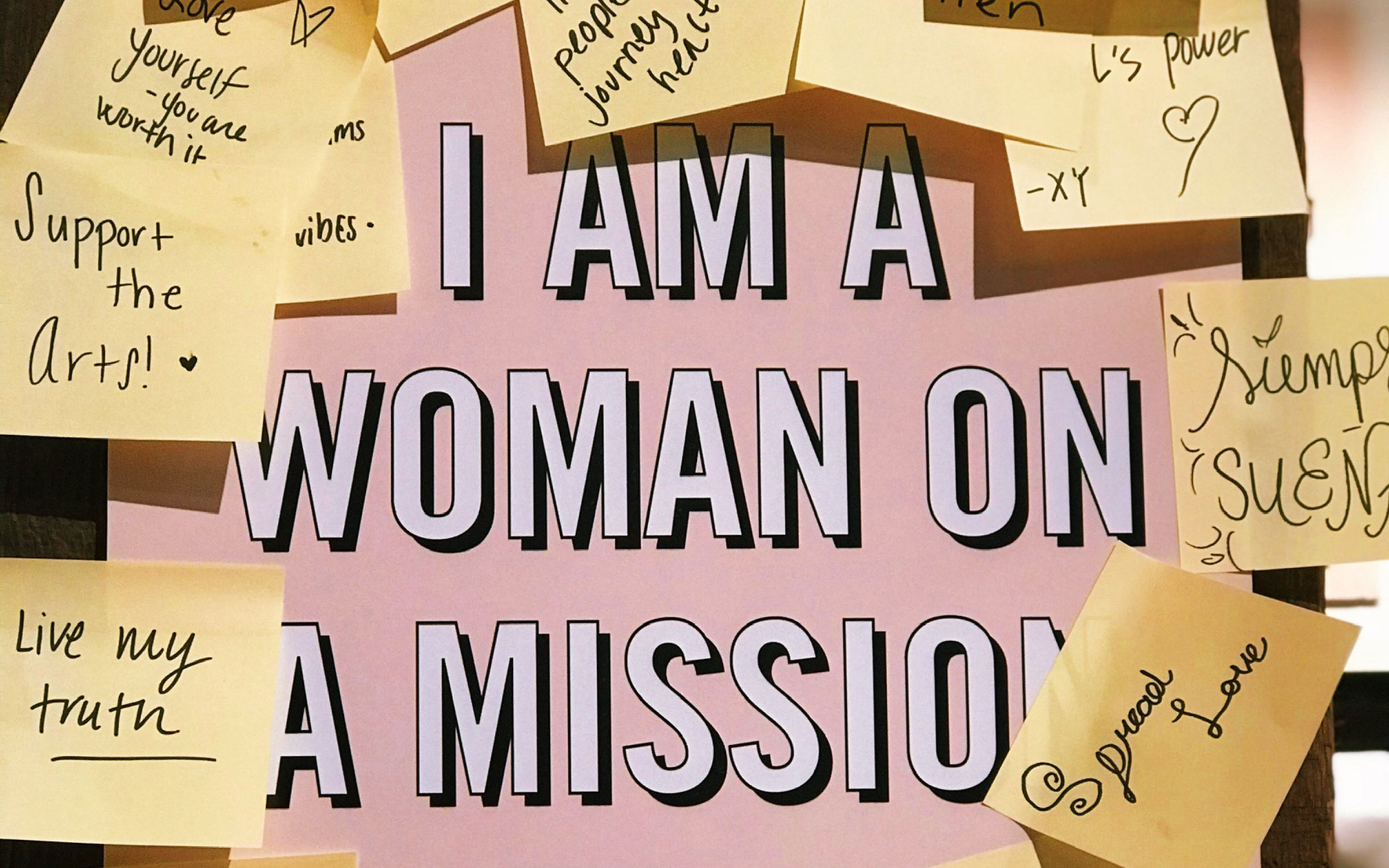 a pink sign reads Woman On a Mission surrounded by yellow sticky notes with inspirational message