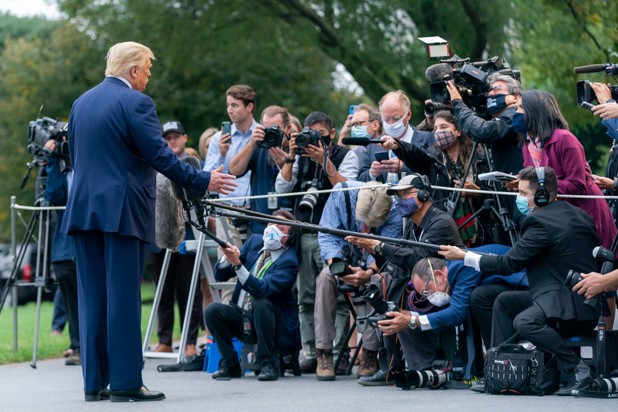 Donald Trump, a white dumpy man wearing a navy blue suit, talks to journalists in front of the White House