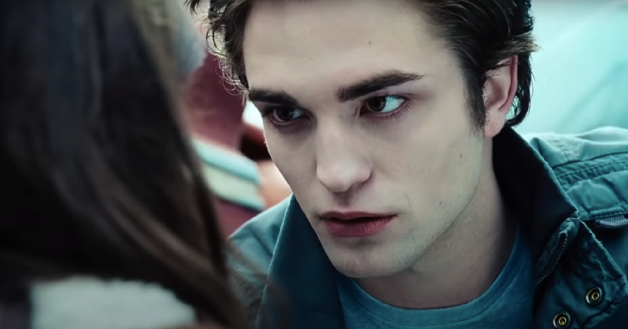 Edward, a very white vampire, leans down to Bella as he saves her from being hit by a car.