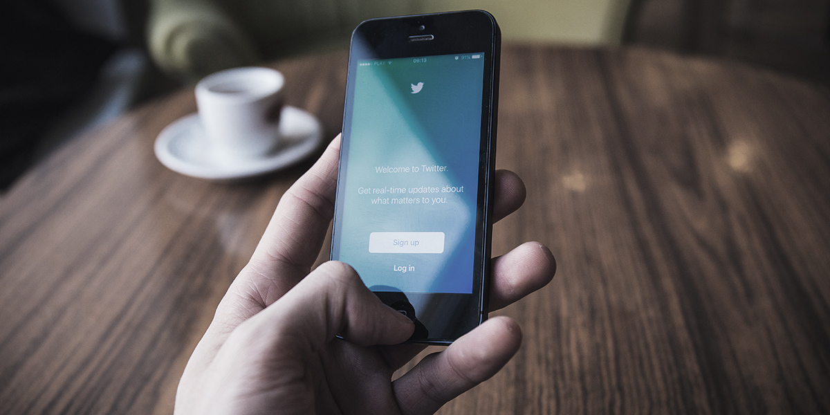 Closeup of a hand holding an iphone with the Twitter app open