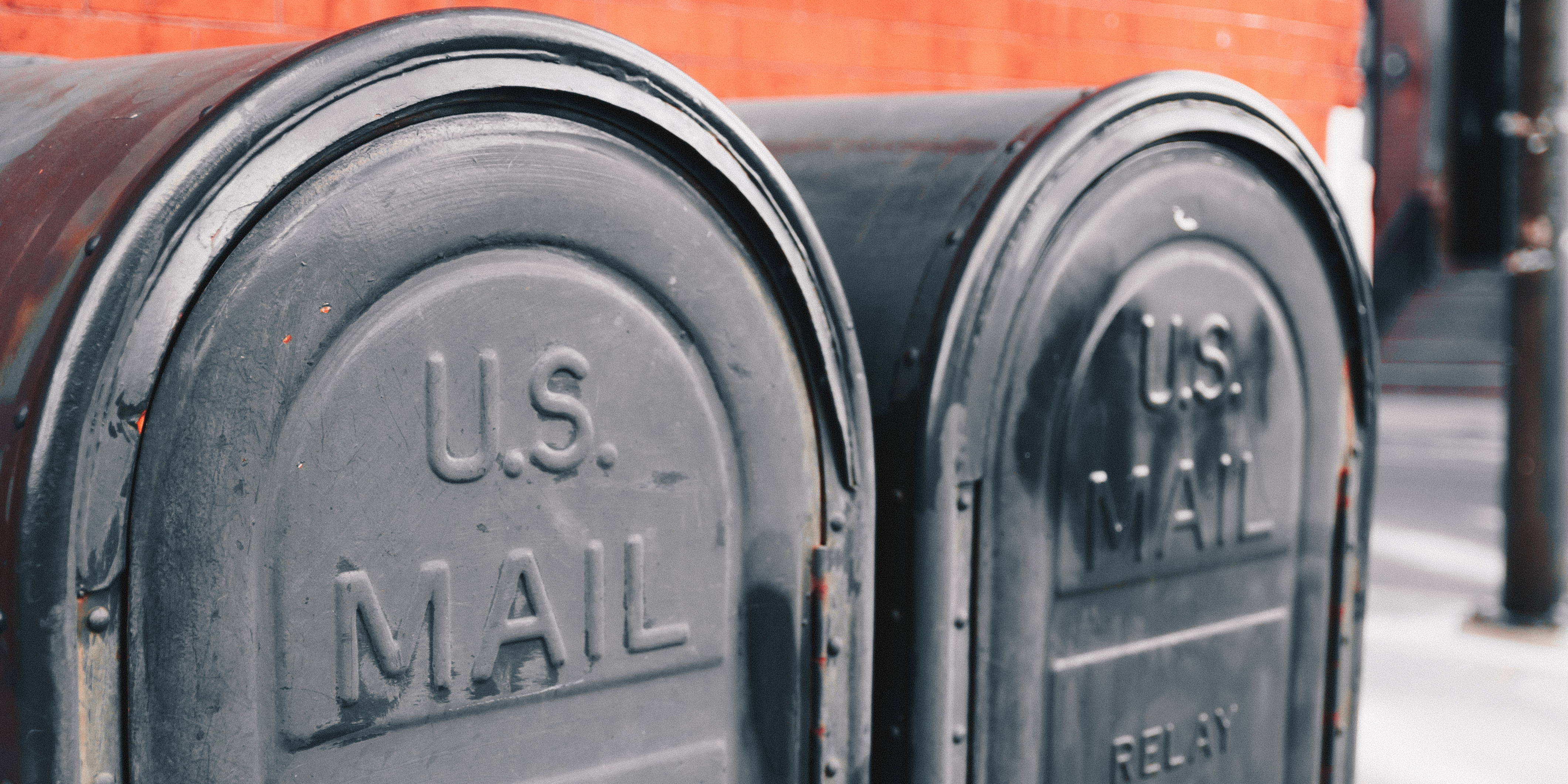 """Two black mailboxes that say """"U.S. Mail"""" side by side on the sidewalk"""