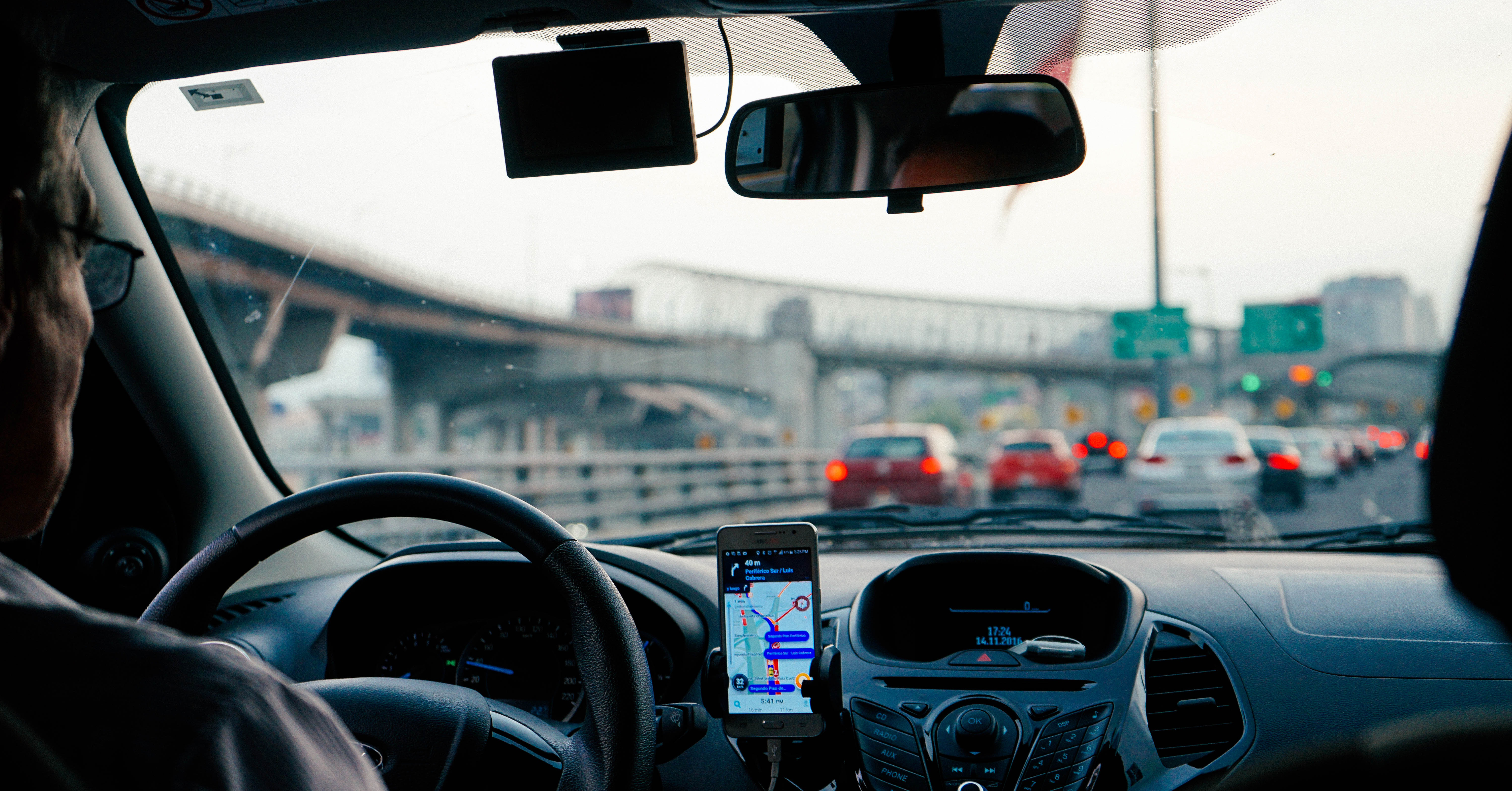 The back of a man in the driver's seat of a car, using a navigation system on his phone