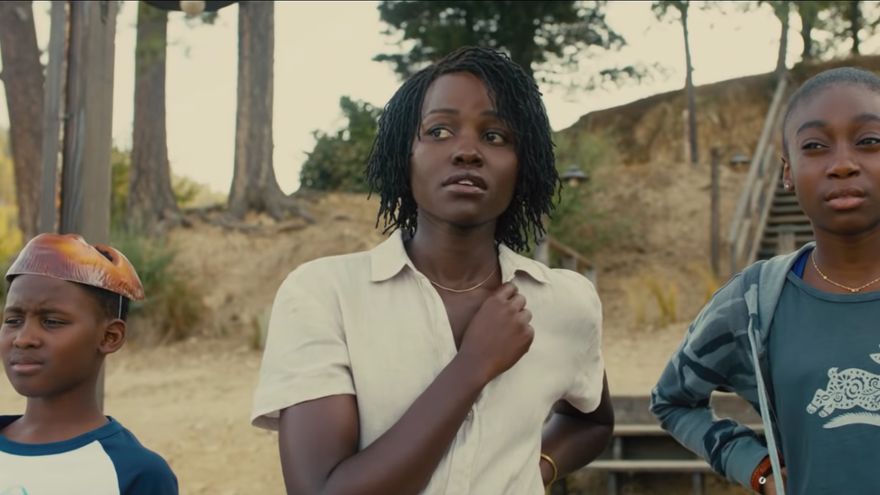 Evan Alex as Jason, Shahadi Wright Joseph as Zora, and Lupita Nyong'o as Adelaide stand in a row on the beach, looking worried
