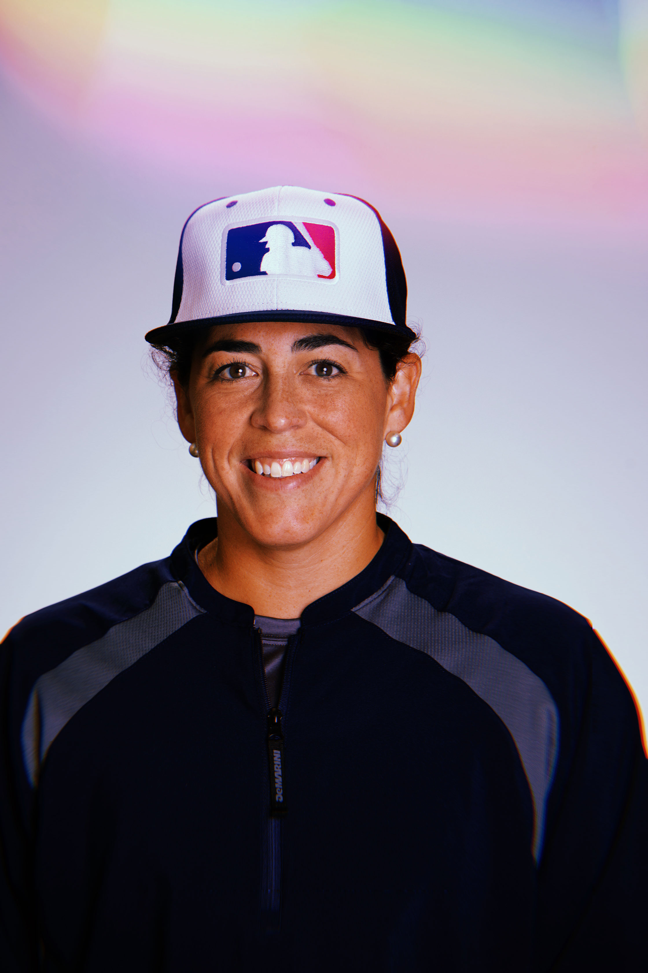 photo of athlete and coach, Veronica Alvarez, a brown woman smiling and wearing a blue activewear top and an MLB baseball cap