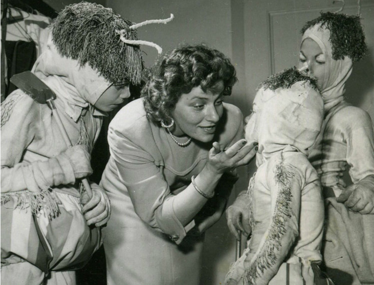 a black and white photo of a white woman playing with three children who are dressed in costumes
