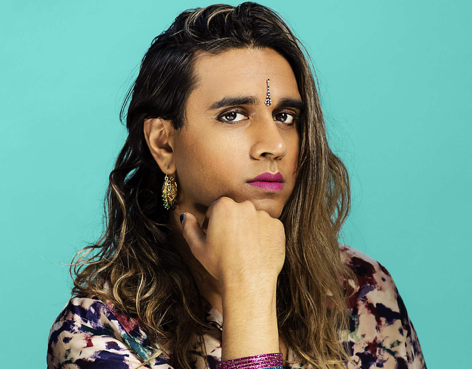 brownskinned woman with long brown hair with an arm on the table in front of a teal blue background
