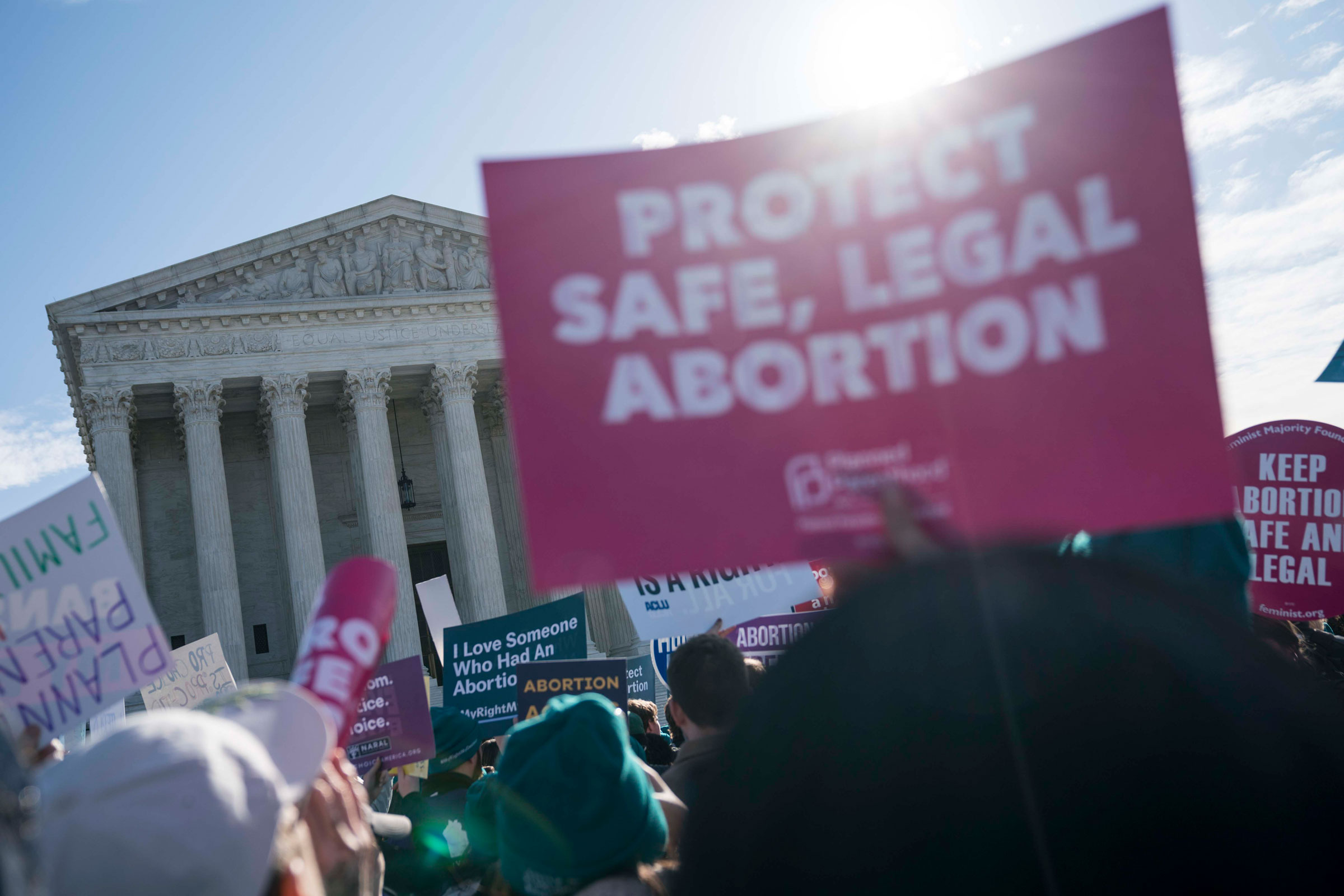 a person in front of the Supreme Court holds a pink Protect Safe, Legal Abortion sing