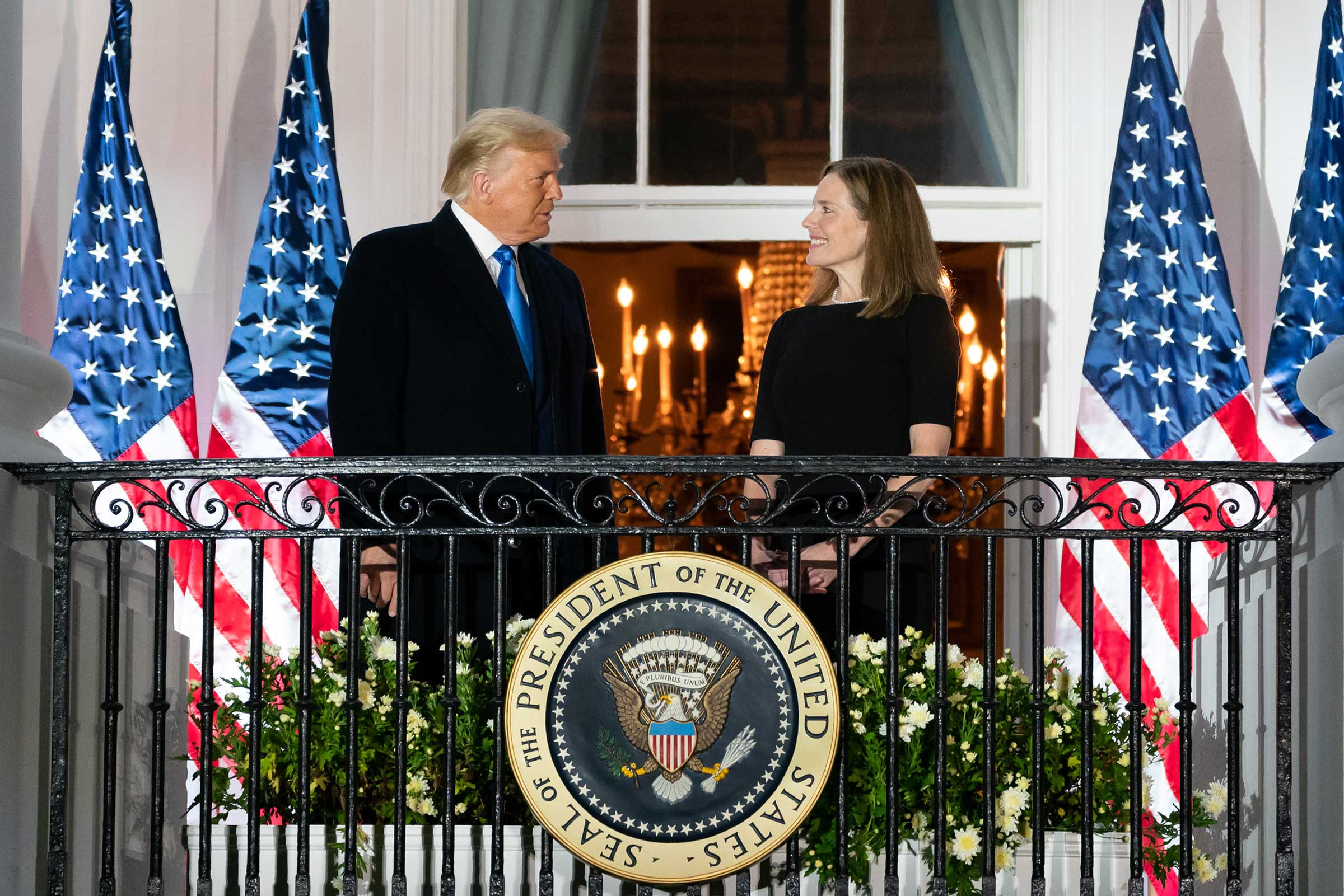 President Donald J. Trump and U.S. Supreme Court Associate Justice Amy Coney Barrett stand on a balcony. They are both white and dressed up.