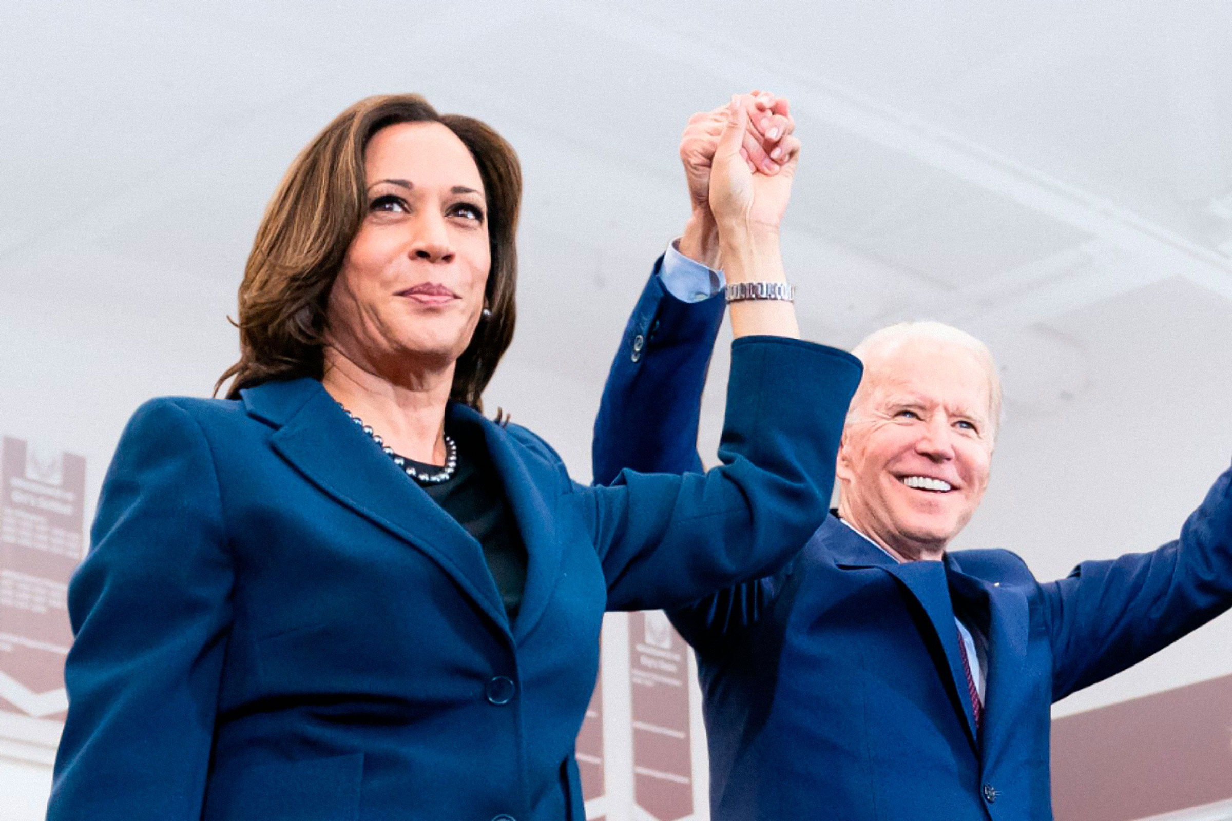 Kamala Harris, a light-skinned Black woman wearing a navy blue suit, holds hands triumphantly with Joe Biden, an older white man with white hair
