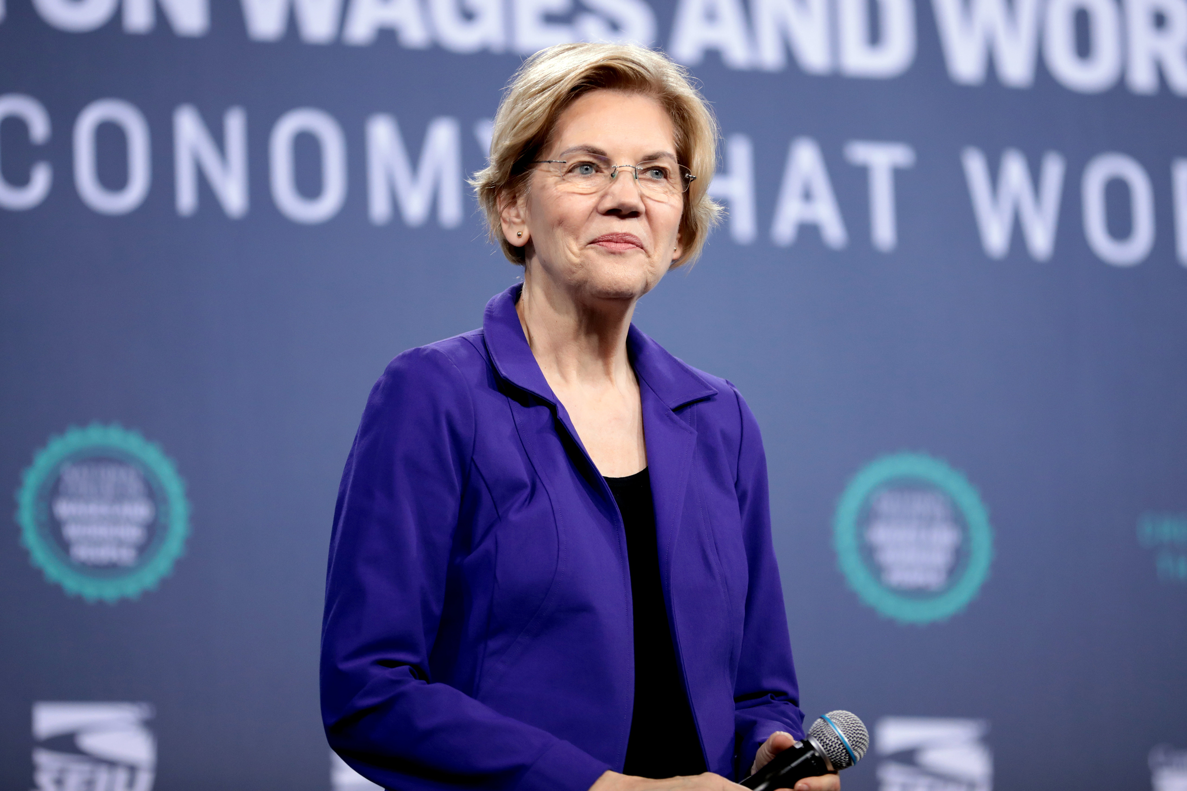 Elizabeth Warren, a white woman with short blond hair, stands, smiling, while holding a microphone.
